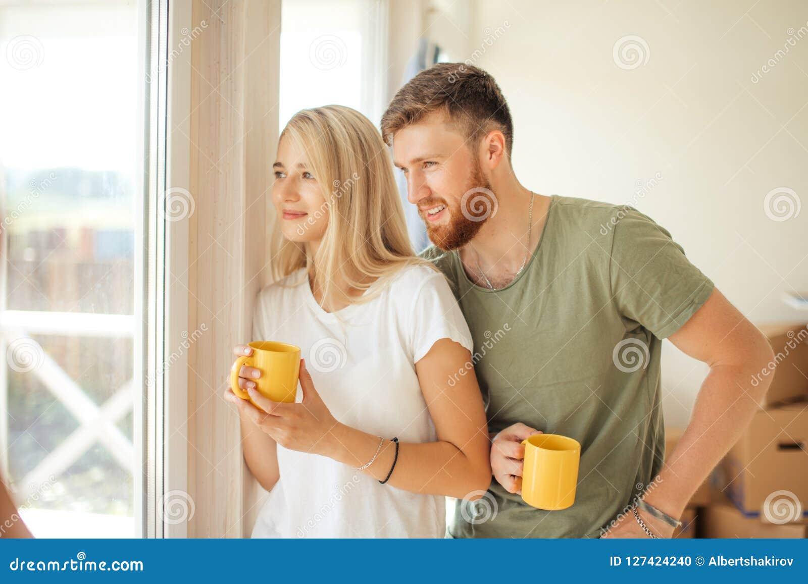 Mężczyzna i kobieta pije herbacianego pobliskiego okno Kupujący mieszkanie lub nowy dom