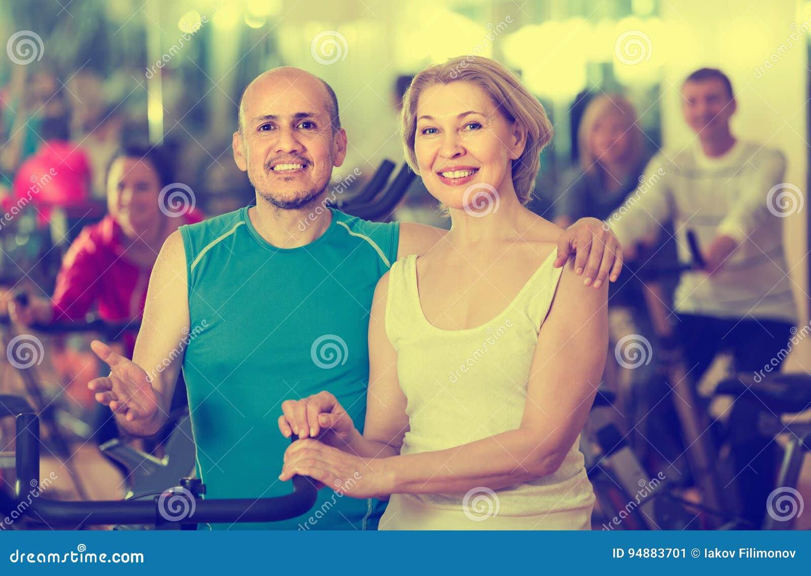 Mężczyzna i kobieta pozuje w ono uśmiecha się i gym