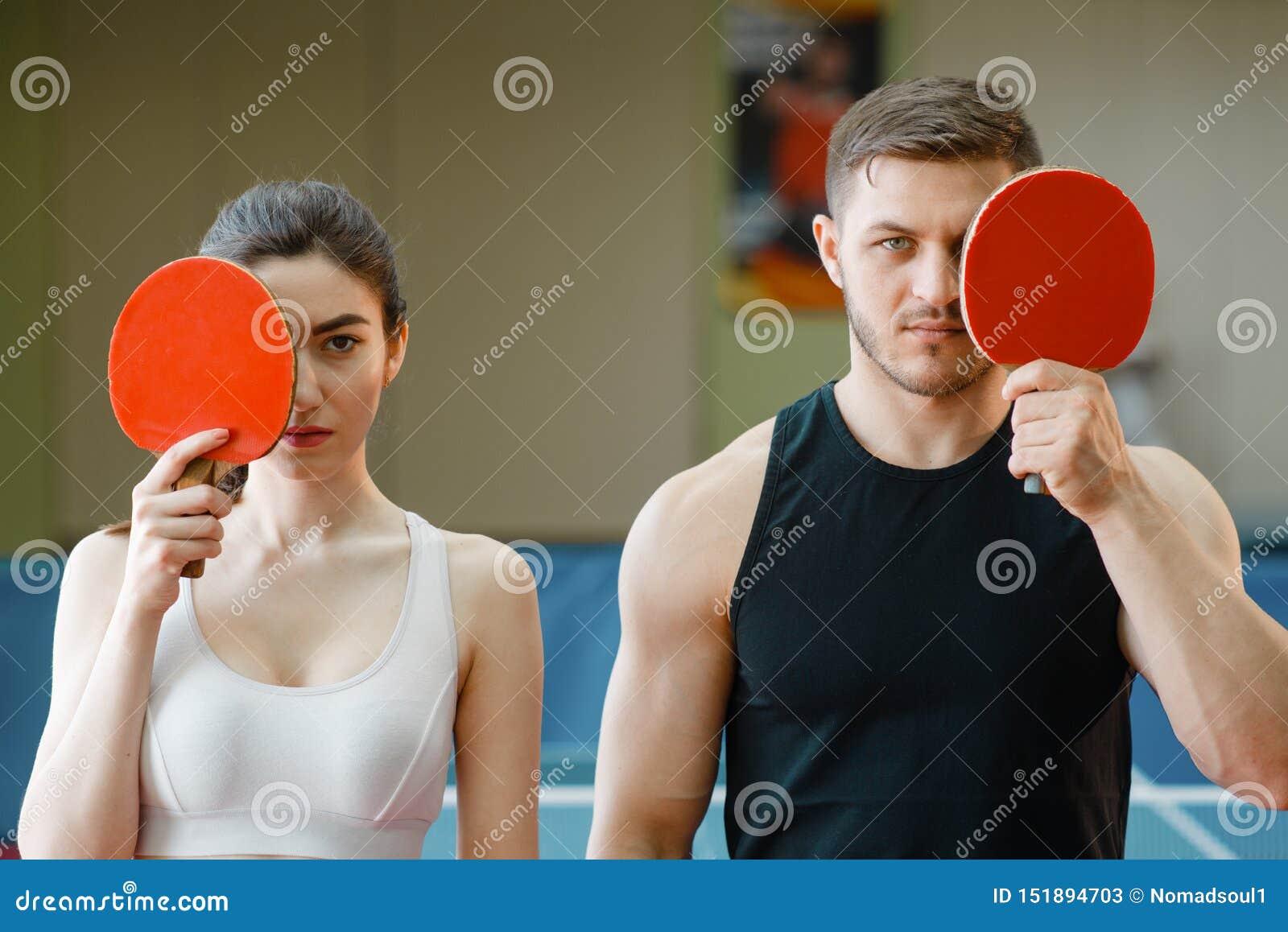 Mężczyzna i kobieta trzymamy śwista pong kanty indoors