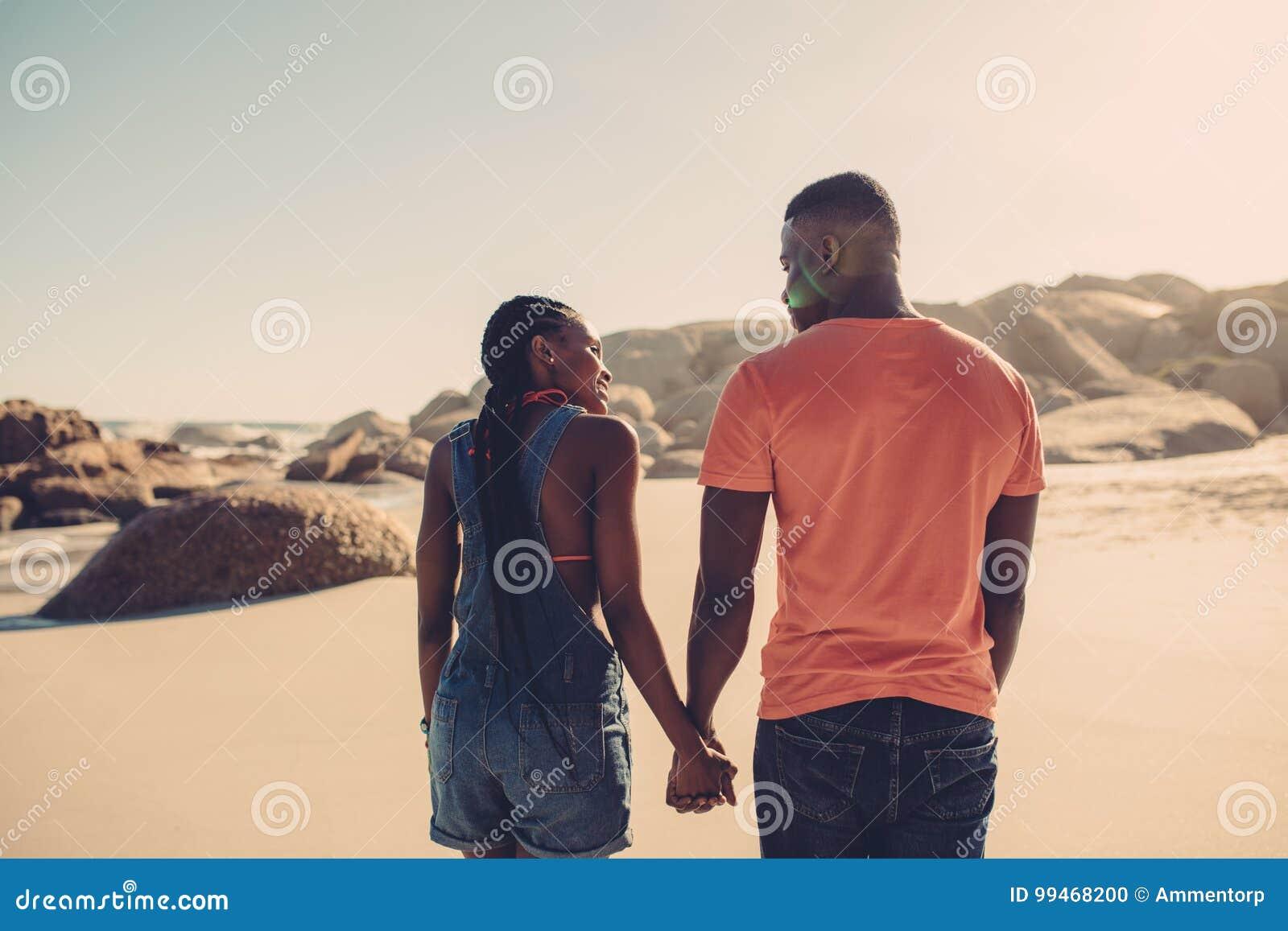 Mężczyzna i kobieta w miłości spaceruje na plaży