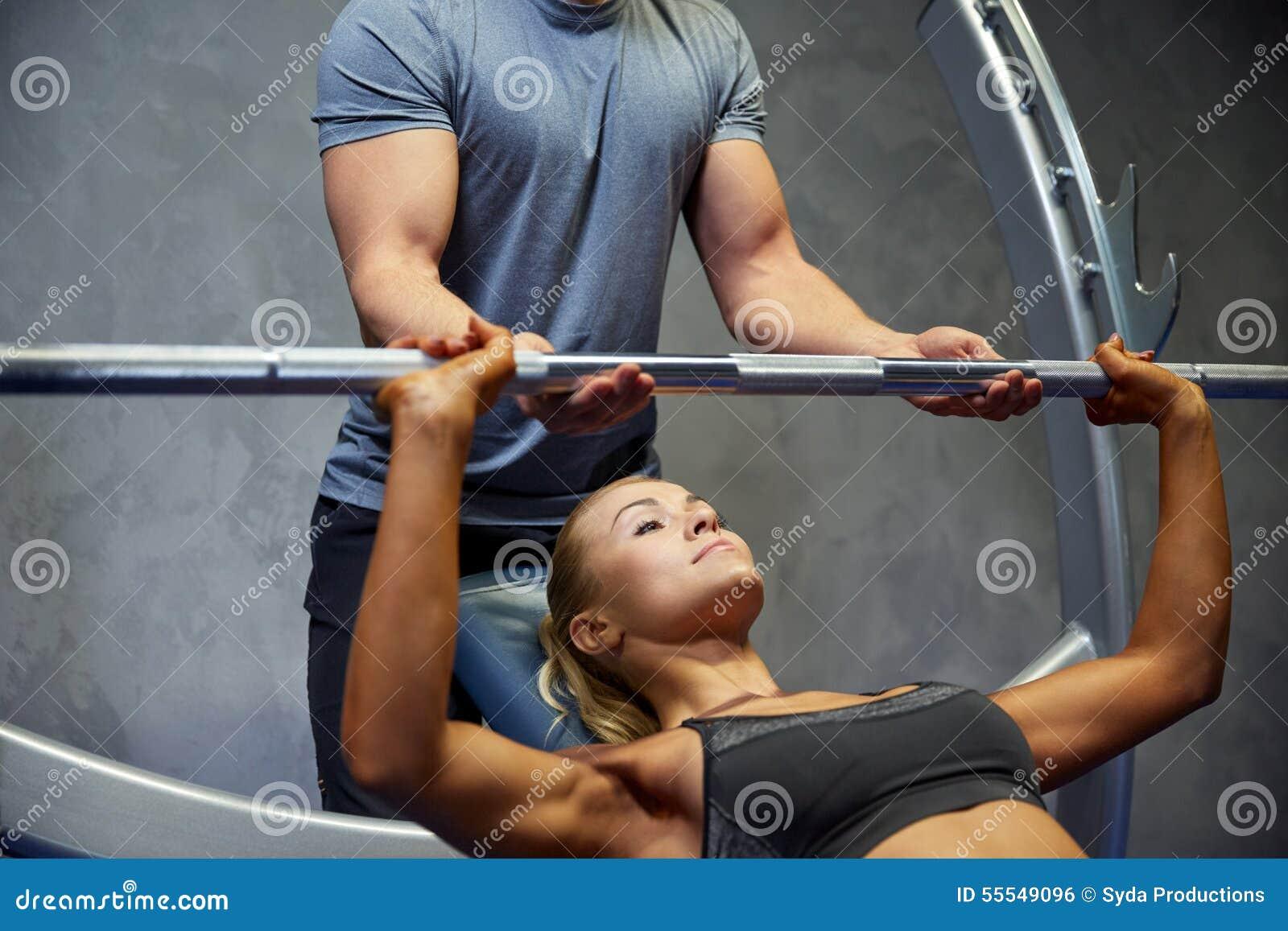 Mężczyzna i kobieta z barbell napina mięśnie w gym