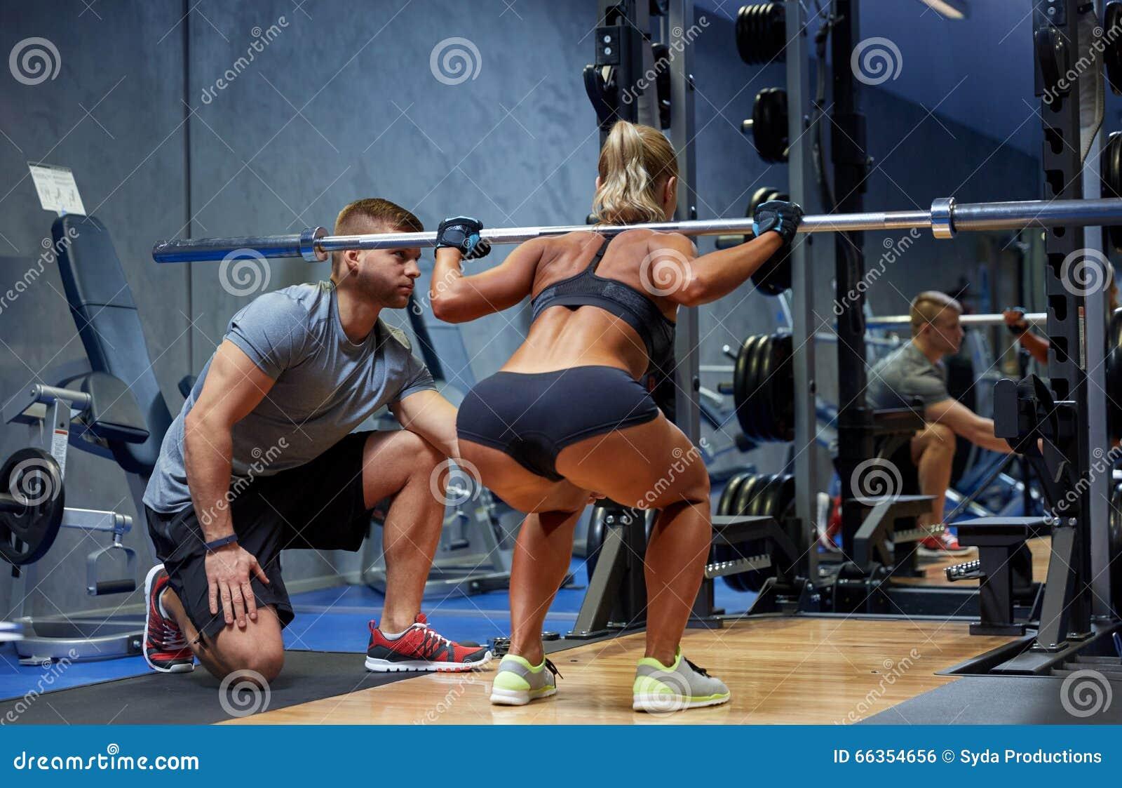 Mężczyzna i kobieta z barem napina mięśnie w gym