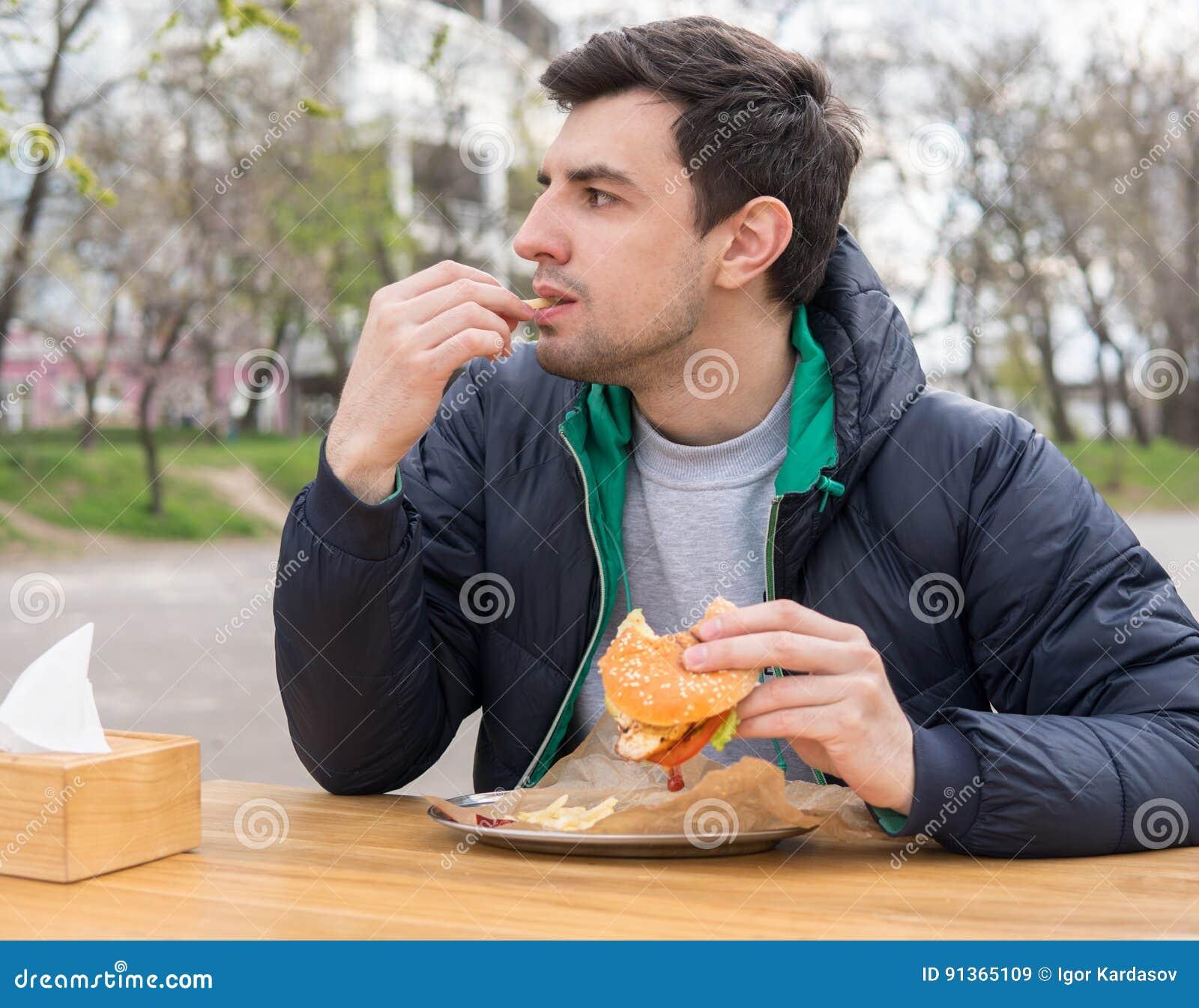Mężczyzna je Francuskich dłoniaki w przekąska barze