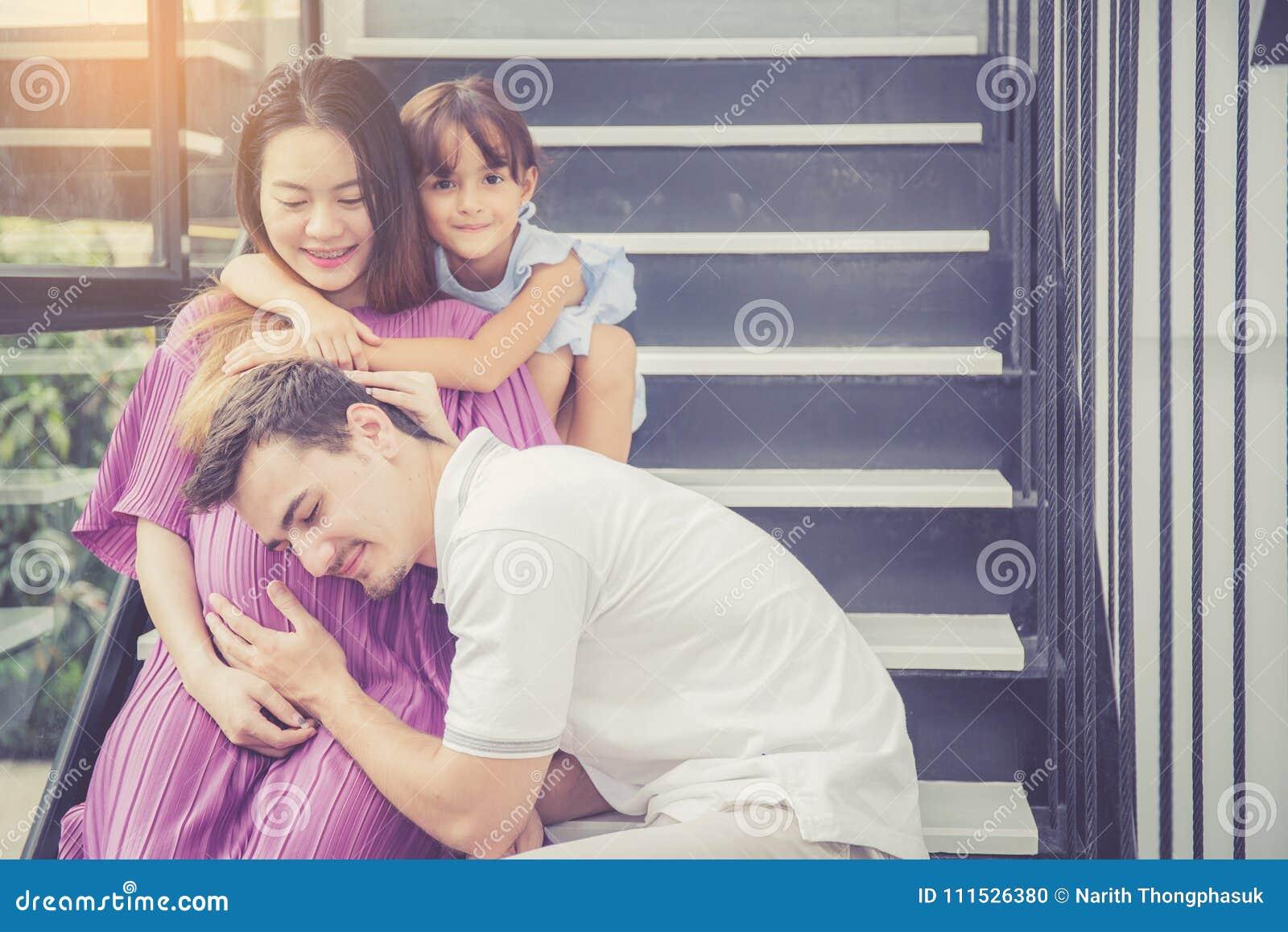 Mężczyzna jest słucha ciężarnego żona, azjatykci przystojny ojciec bierze, oczekuje i opieka dzieciaka z parą i matki macierzyńsk