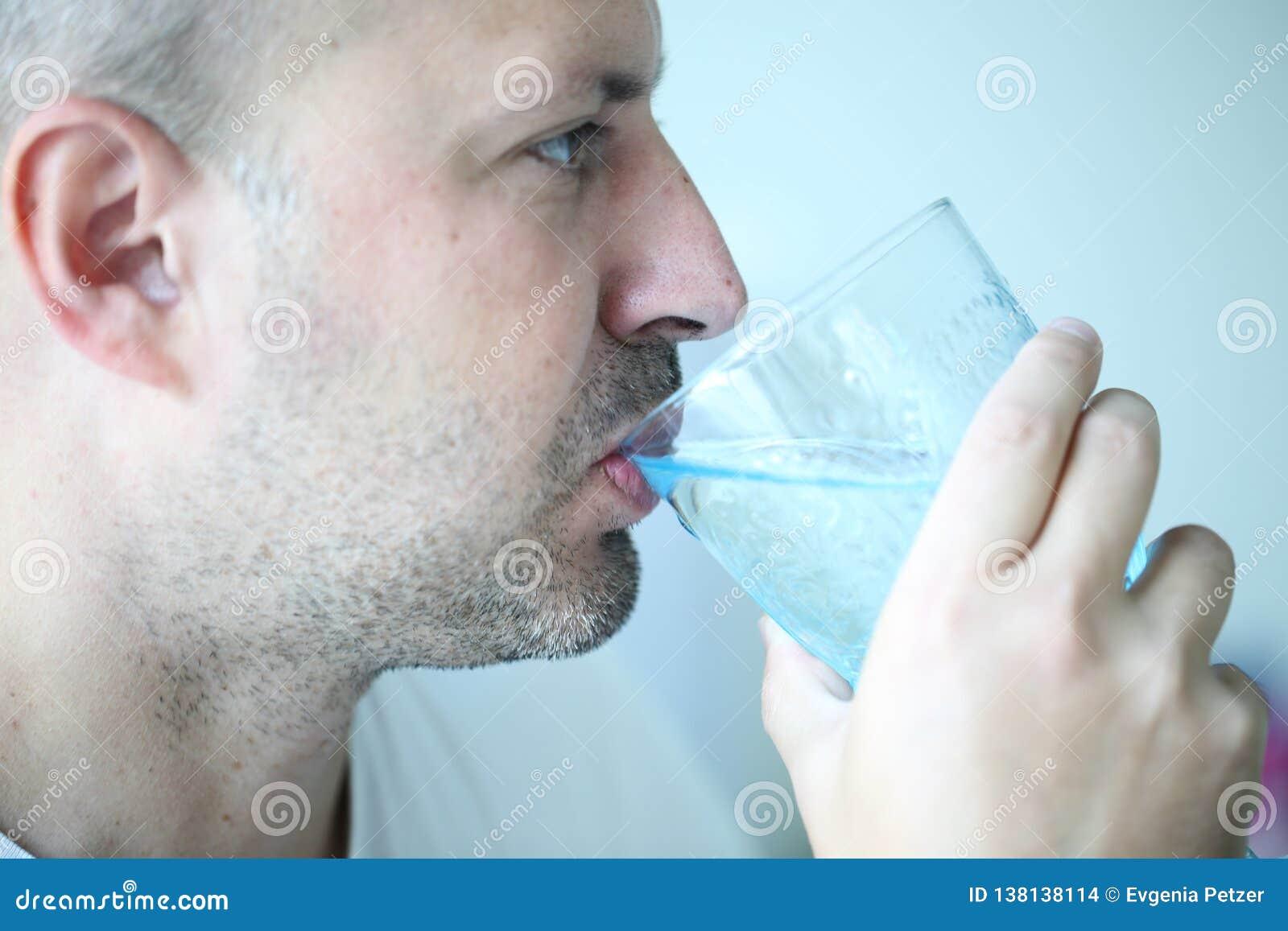 Mężczyzna jest wodą pitną od pięknego błękitnego szkła