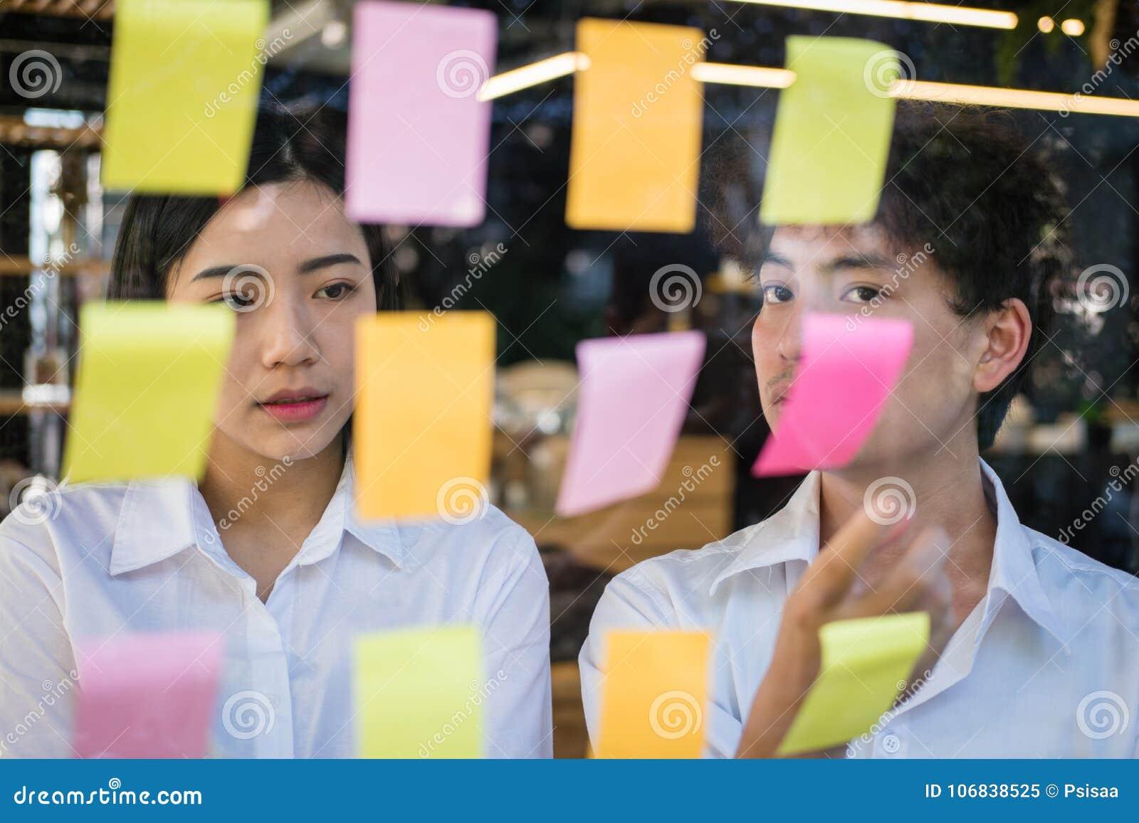 Mężczyzna & kobieta dyskutuje kreatywnie pomysł z adhezyjnymi notatkami na glas