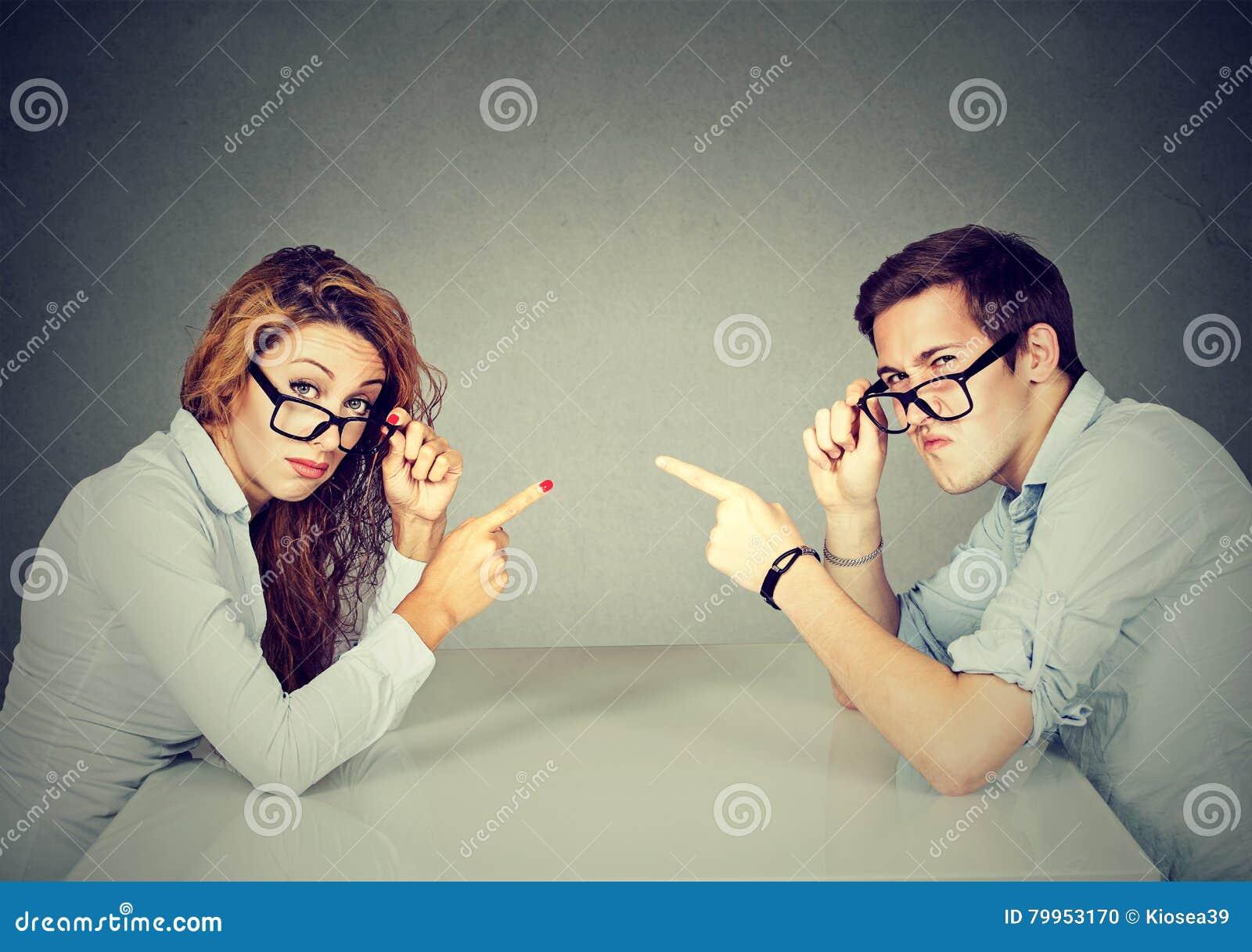 Mężczyzna kobieta wskazuje palce przy each inny wini each inny