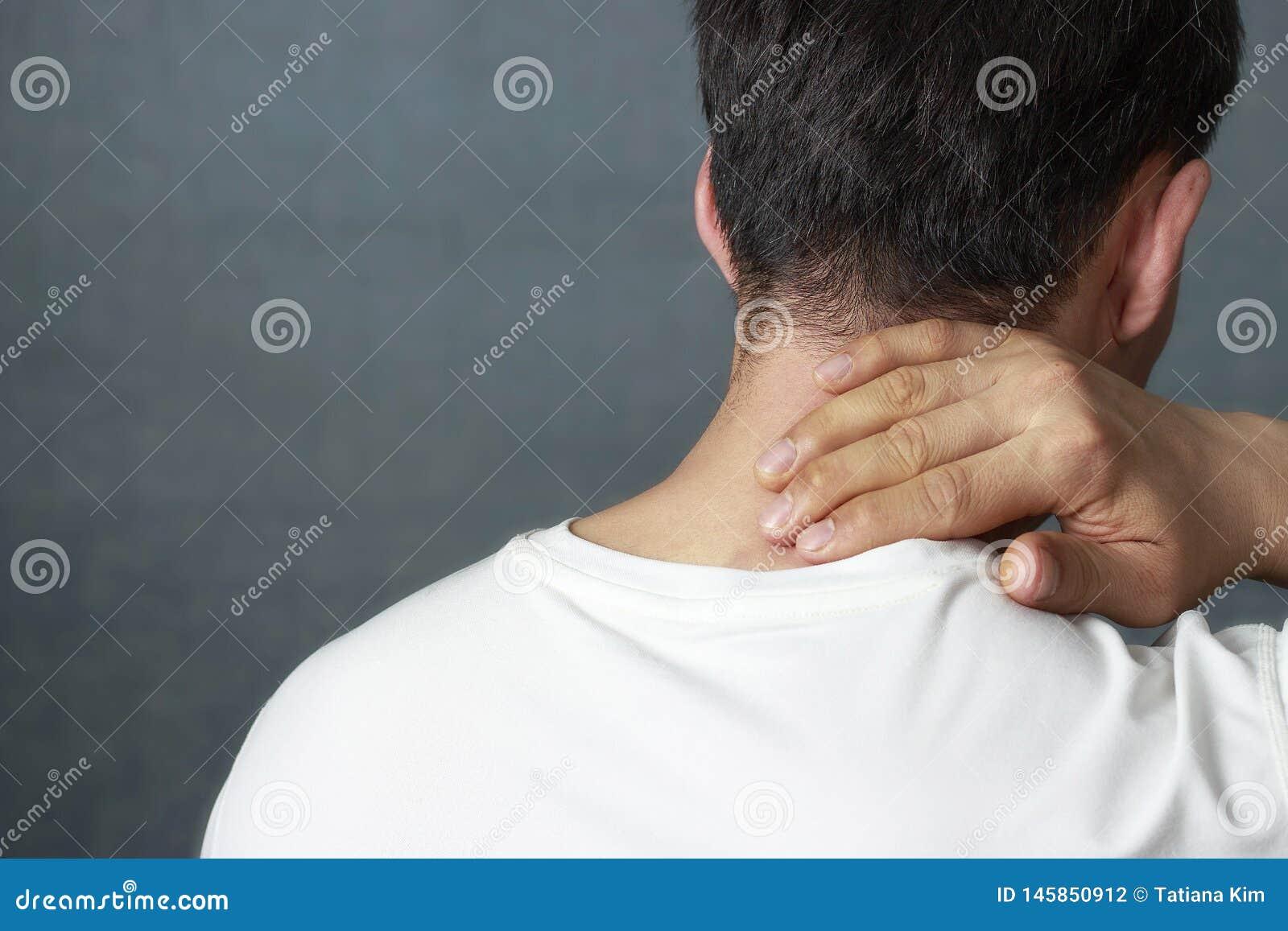 Mężczyzna masuje bolesną szyję, w górę, tylni widok