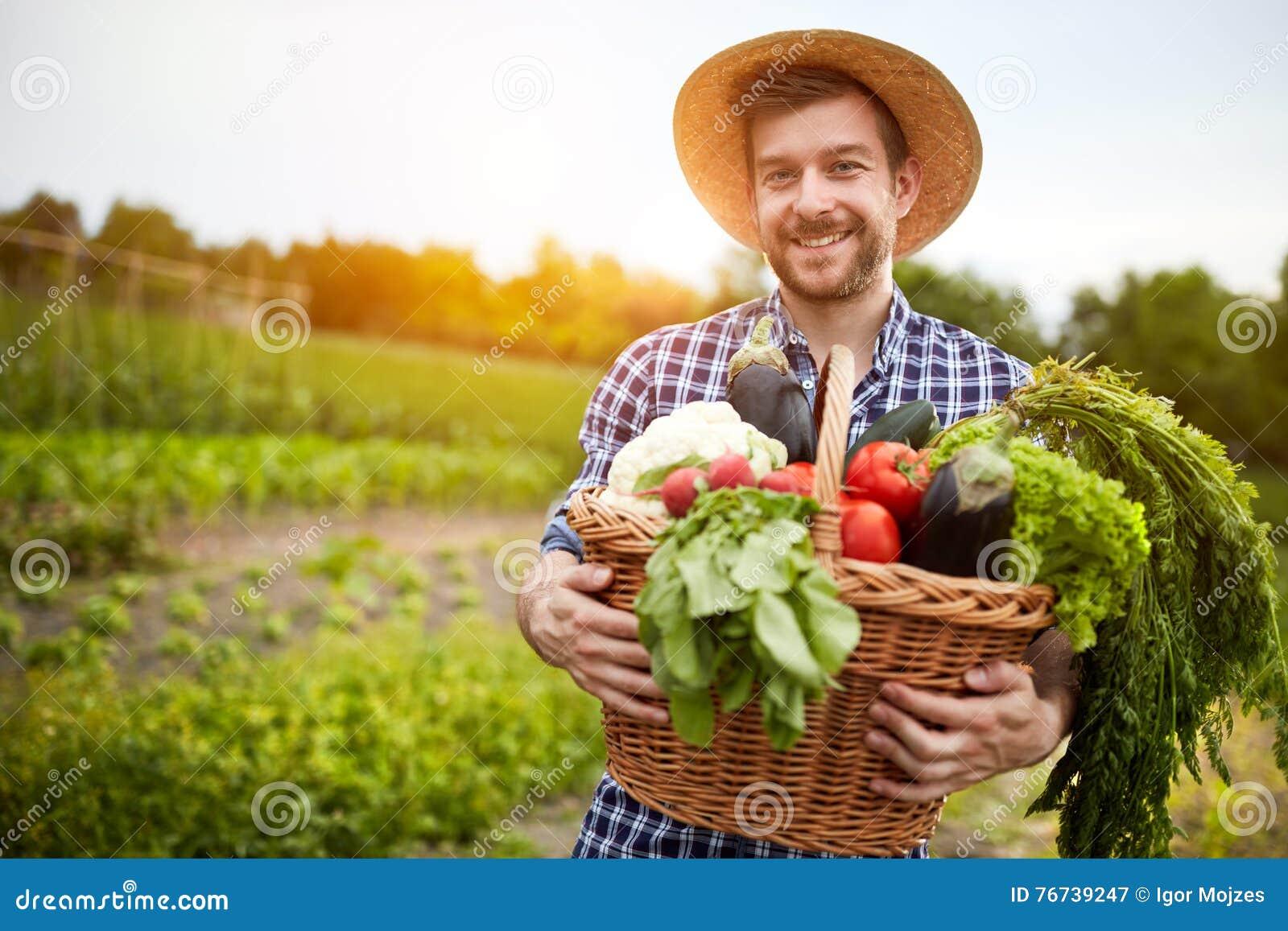 Mężczyzna mienia kosz z organicznie warzywami