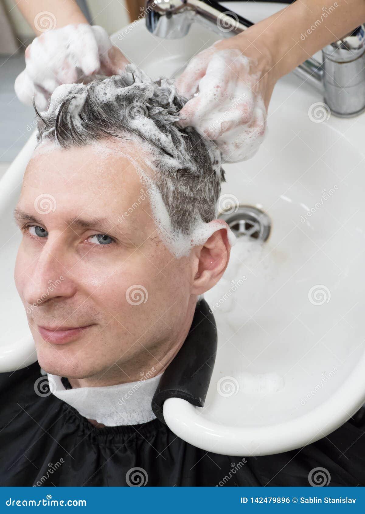Mężczyzna myje jego włosy po ostrzyżenia