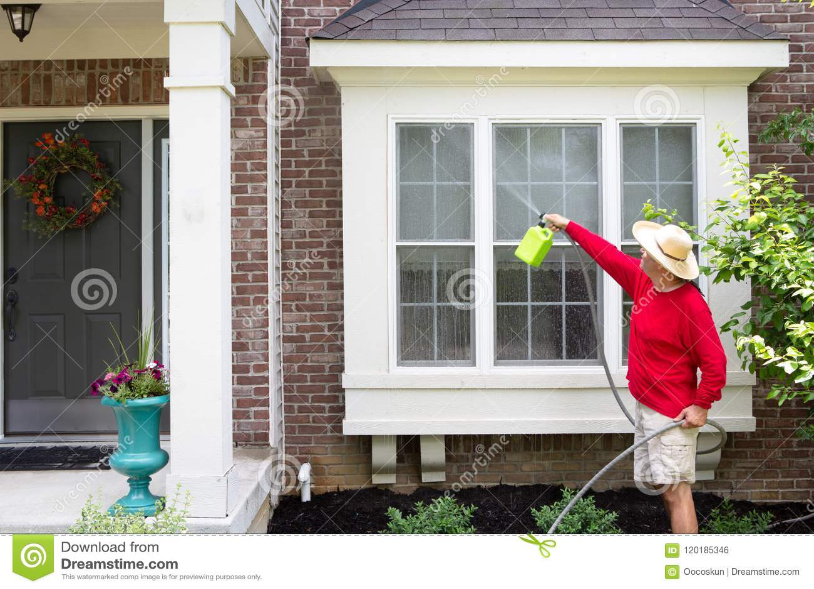 Mężczyzna myje podpalanych okno lub garbek