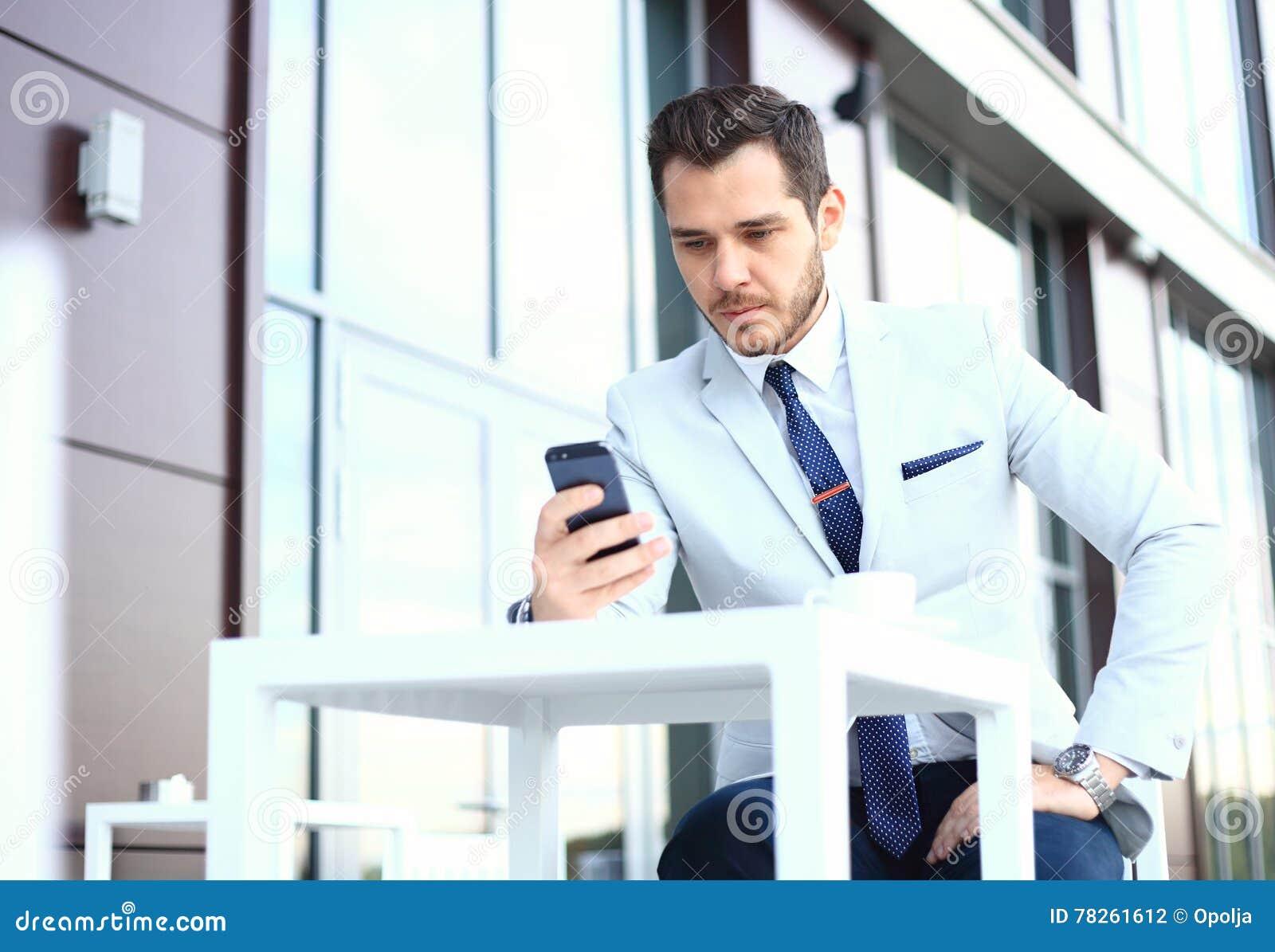 Mężczyzna na smartphone - młody biznesowy mężczyzna opowiada na mądrze telefonie Przypadkowy miastowy fachowy biznesmen używa mob