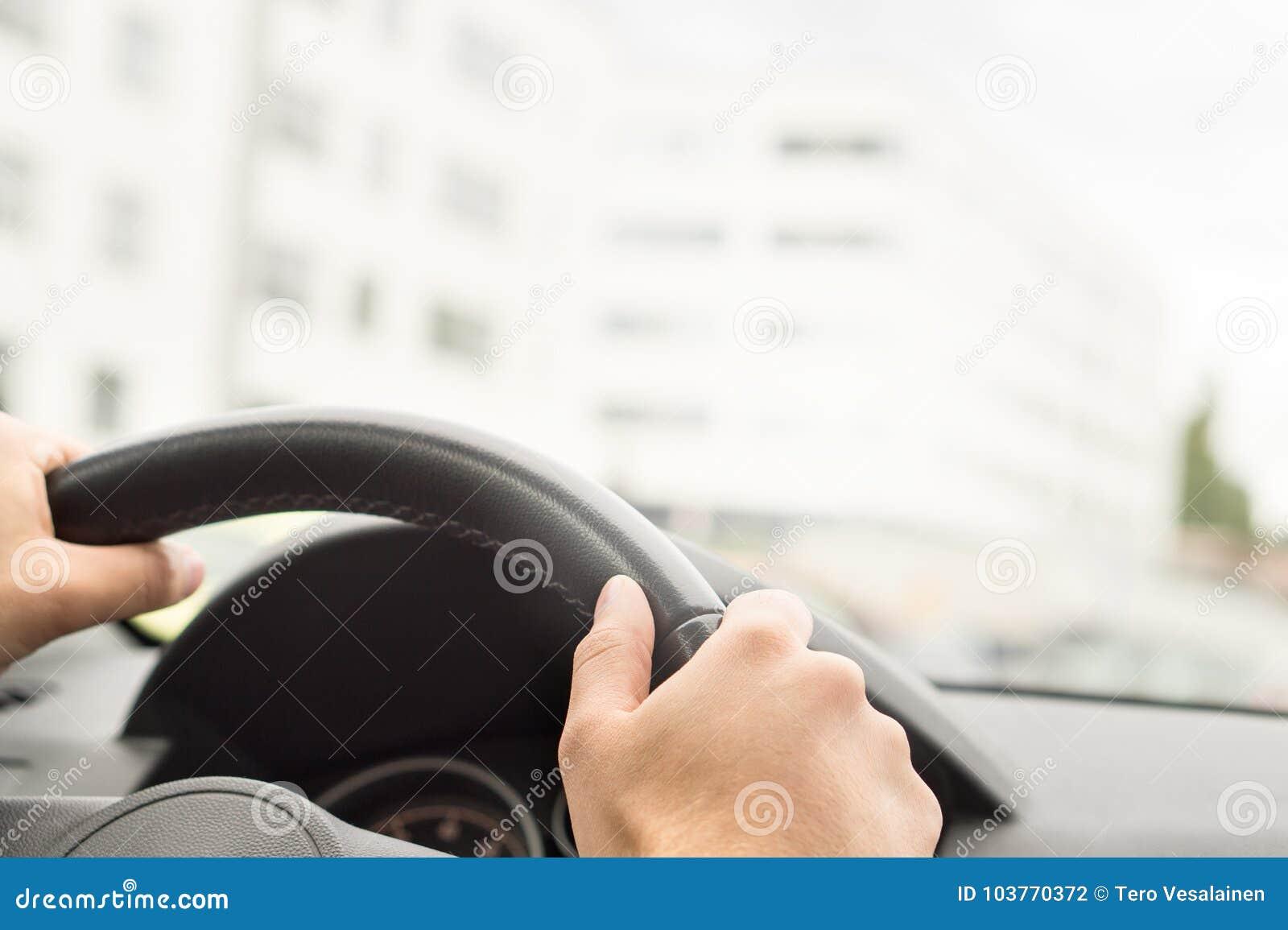 Mężczyzna napędowy samochód w mieście Kierowcy mienia kierownica