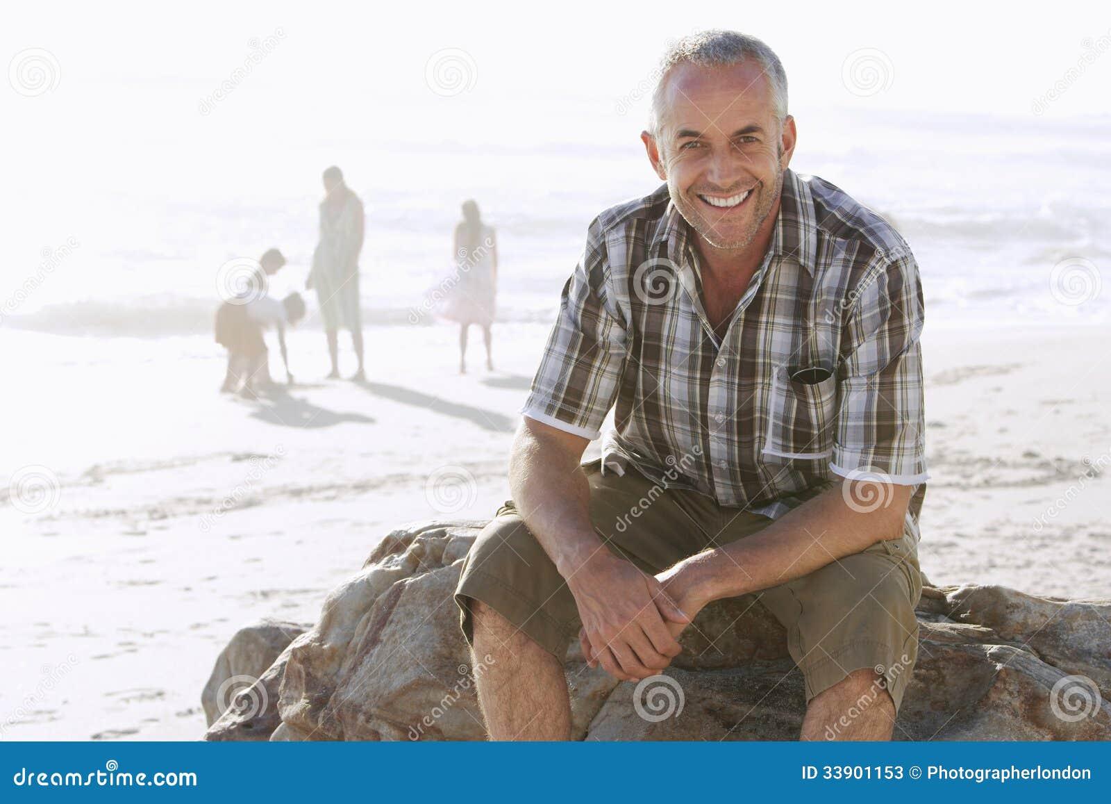 Mężczyzna obsiadanie Na skale Podczas gdy rodzina Cieszy się Przy plażą