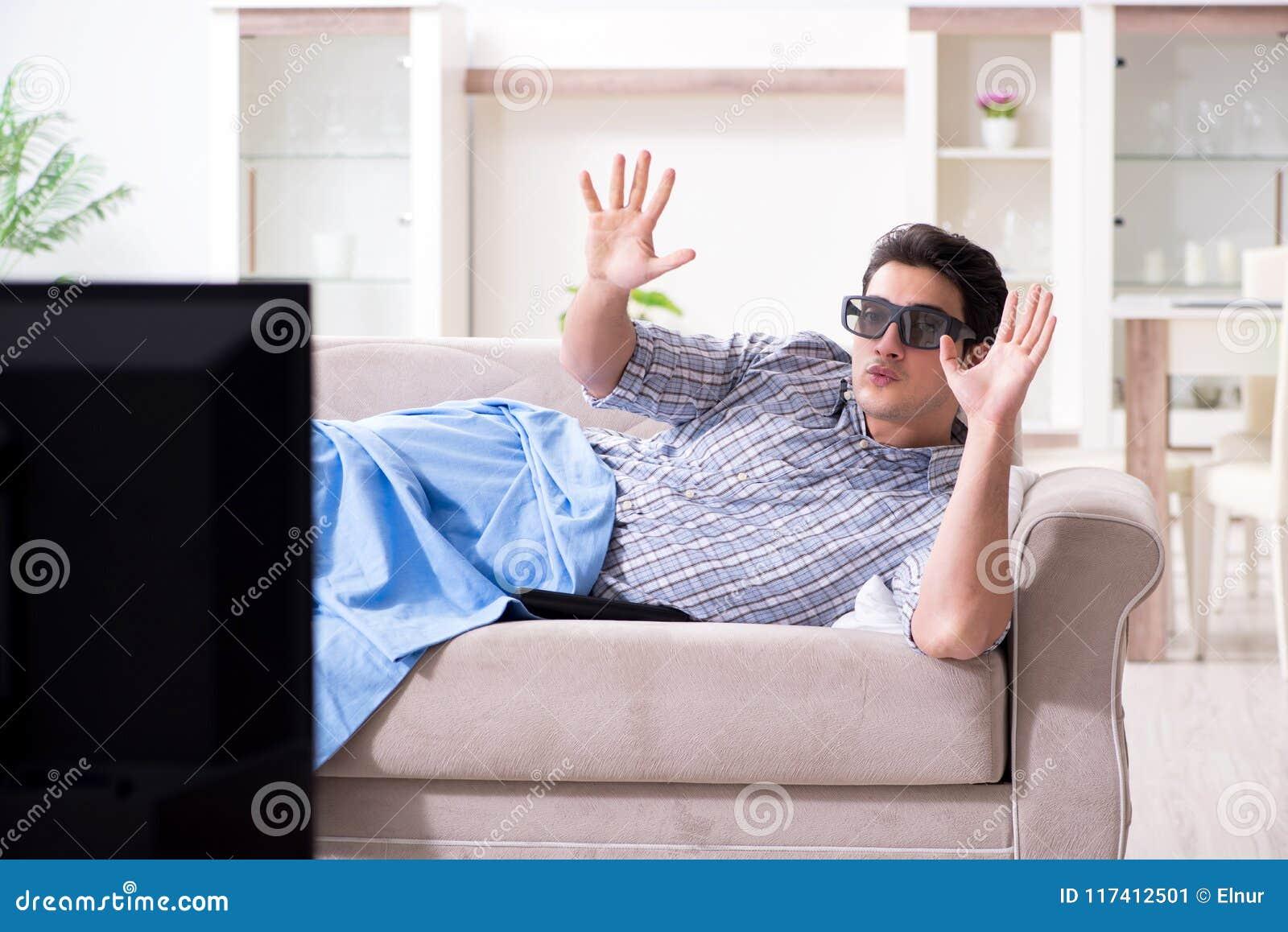 Mężczyzna ogląda 3d tv w domu