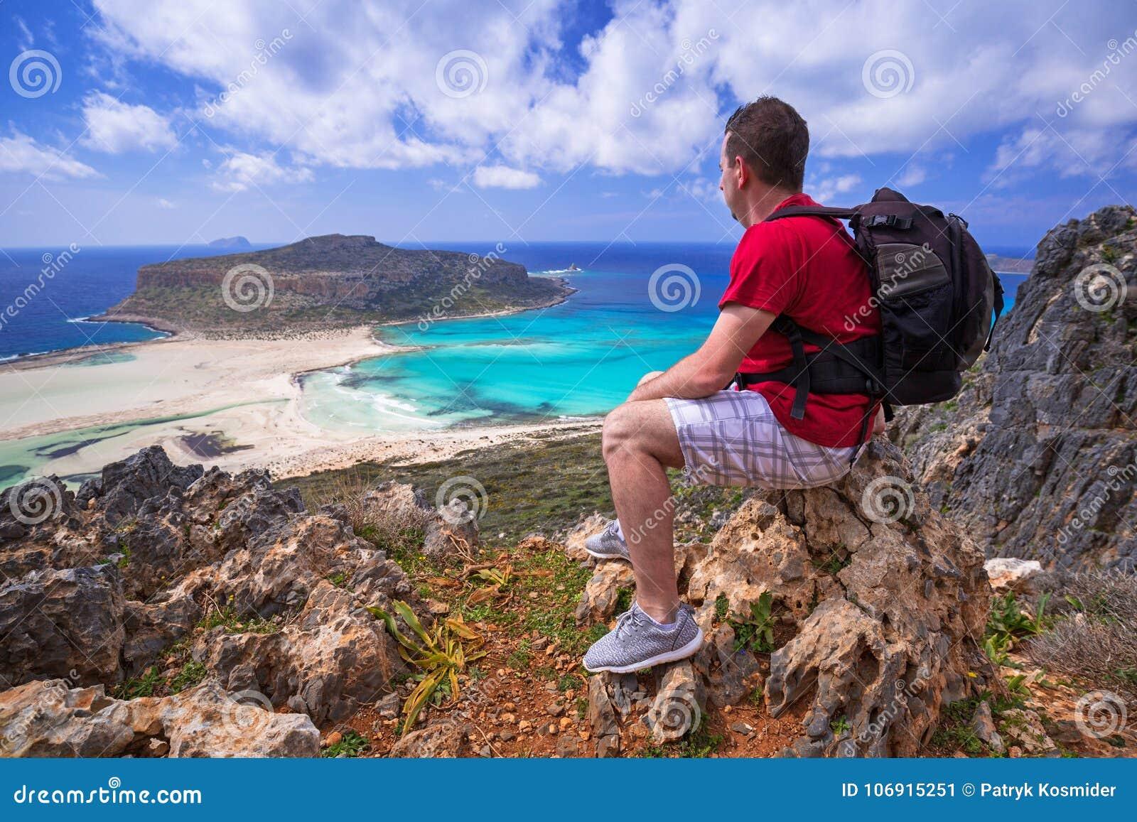 Mężczyzna ogląda piękną Balos plażę na Crete z plecakiem