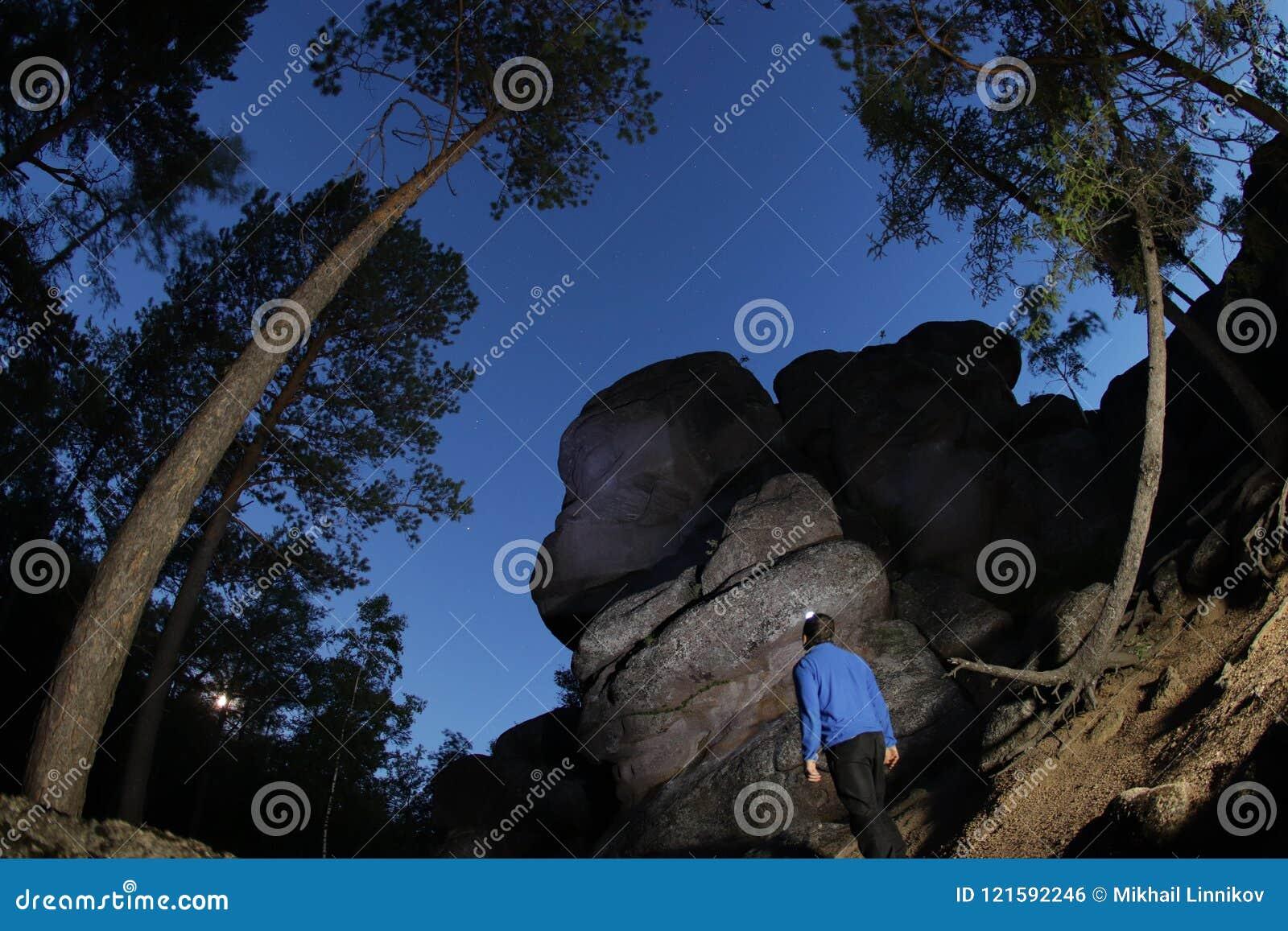 Mężczyzna osamotneni stojaki przy stopą góra i patrzeją up przy niewiadomym niebem Gwiaździsty niebo w Syberyjskiej naturze