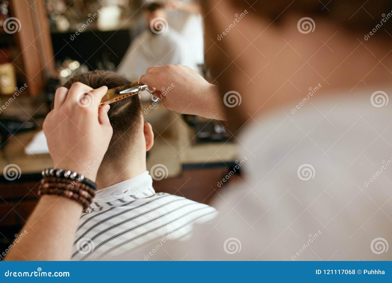Mężczyzna ostrzyżenie Fryzjera męskiego rozcięcia mężczyzna ` s włosy W fryzjera męskiego sklepie