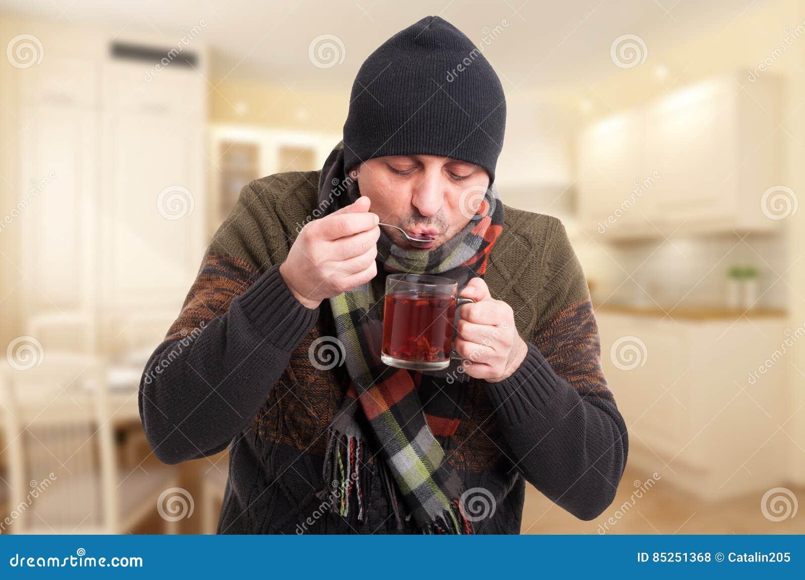 Mężczyzna pije gorącej herbaty z zimnym lub grypa