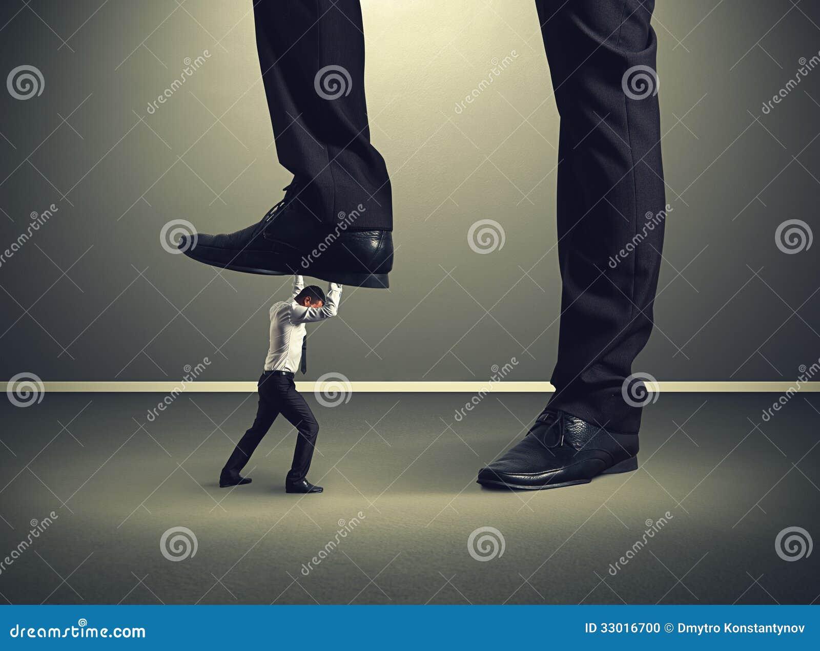 Mężczyzna pod dużą nogą jego szef