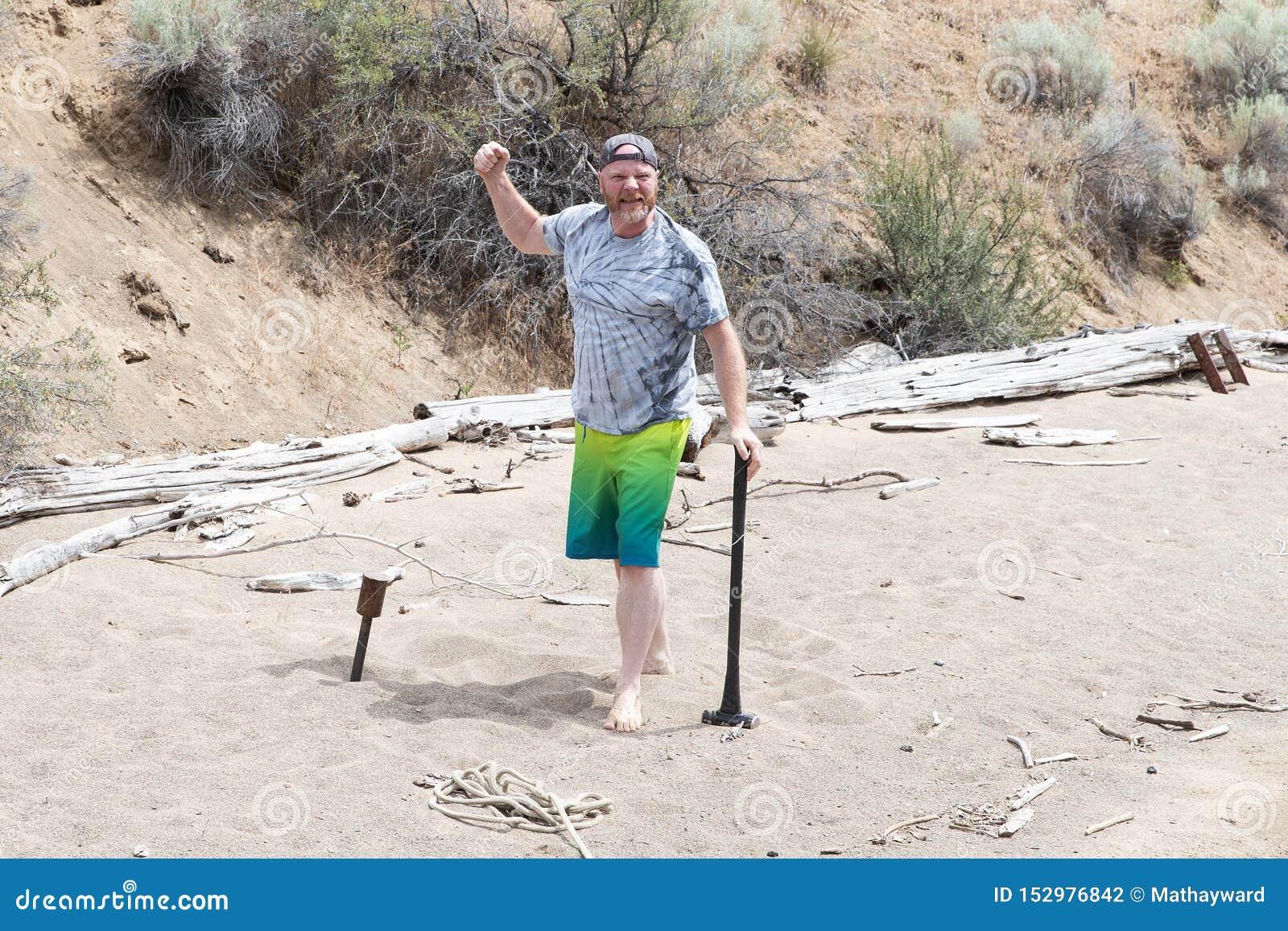 Mężczyzna podnosi jego pięść w powietrzu po tym jak jadący metalu stos w piaskowatą plażę z pełnozamachowym młotem