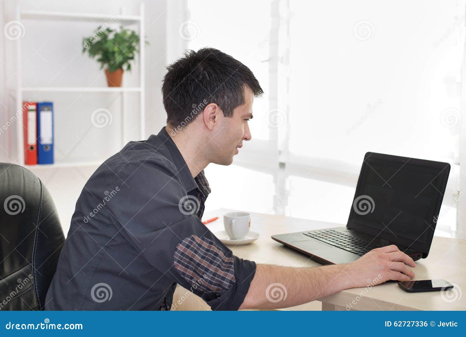 Mężczyzna pracuje na laptopie w biurze