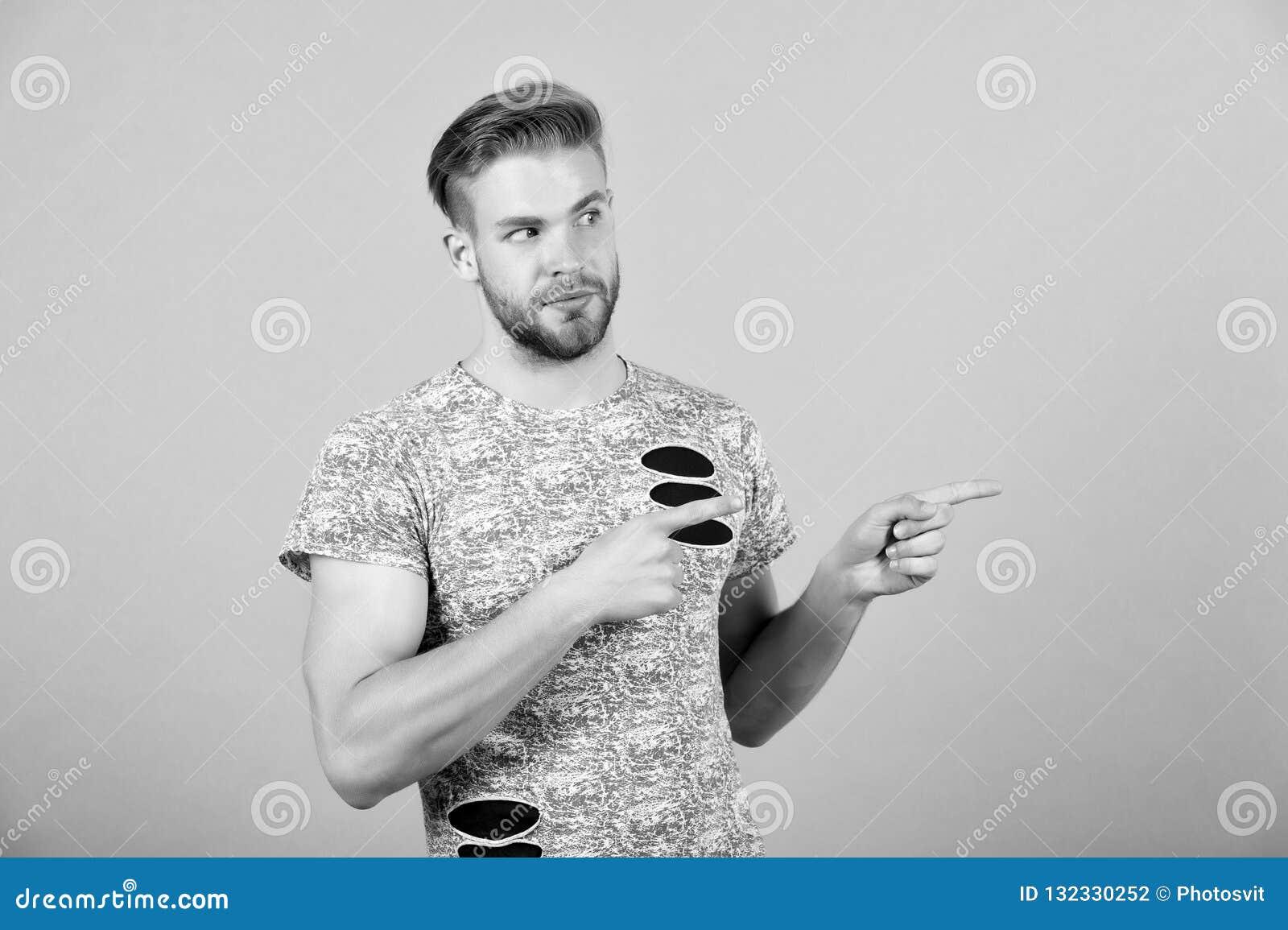 Mężczyzna przedstawia produkt na popielatym tle Macho z brodatym twarz punktu palca gestem Prezentacja, ogłoszenie