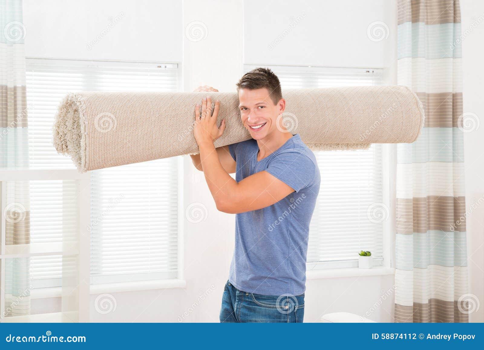 Mężczyzna przewożenie Staczający się dywan