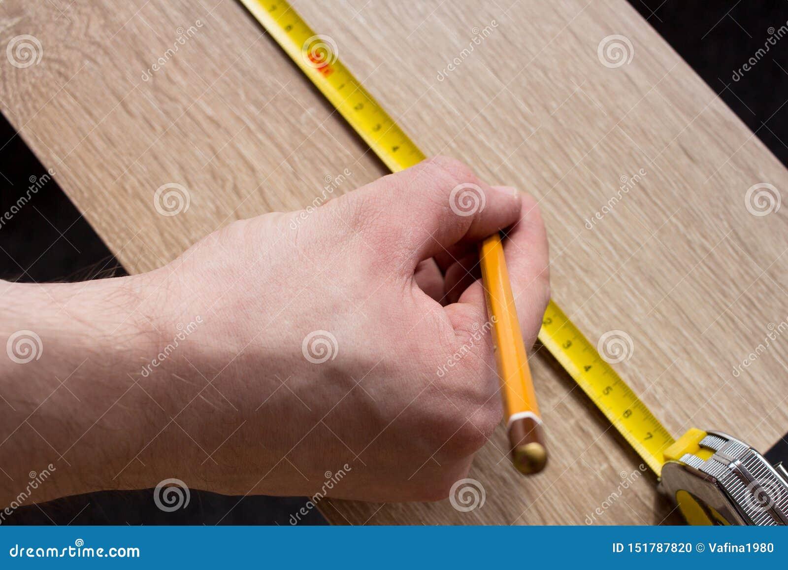 Mężczyzna ręk pomiarowa drewniana deska z taśmy linią