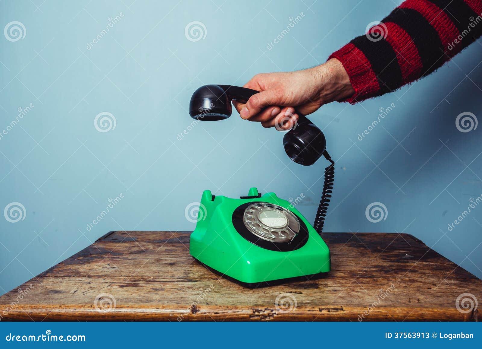 Mężczyzna ręka podnosi up telefon