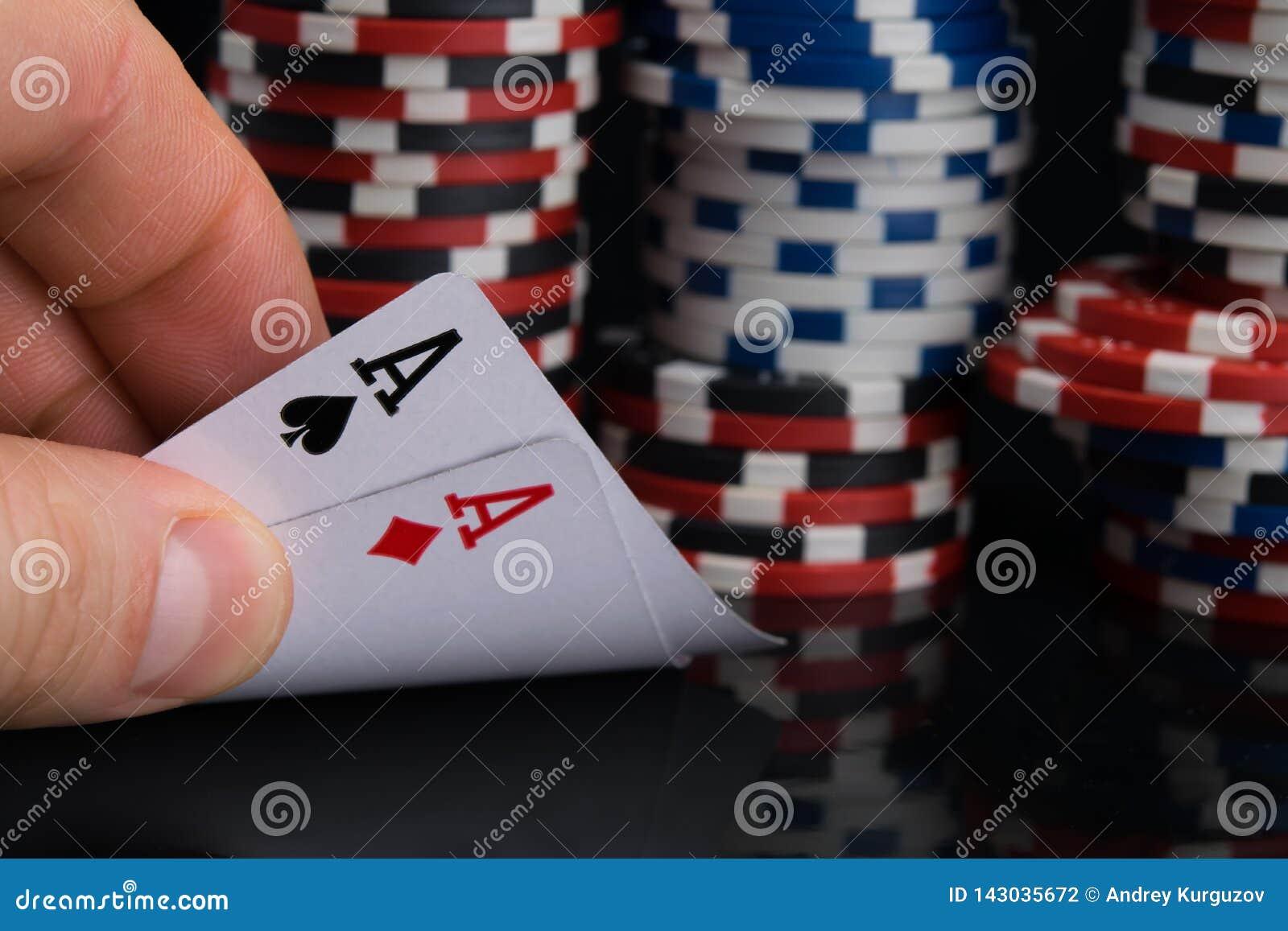 Mężczyzna ręka sprawdza karty dla bawić się w kasynie, otwiera dwa as, przeciw tłu ampuła zakład
