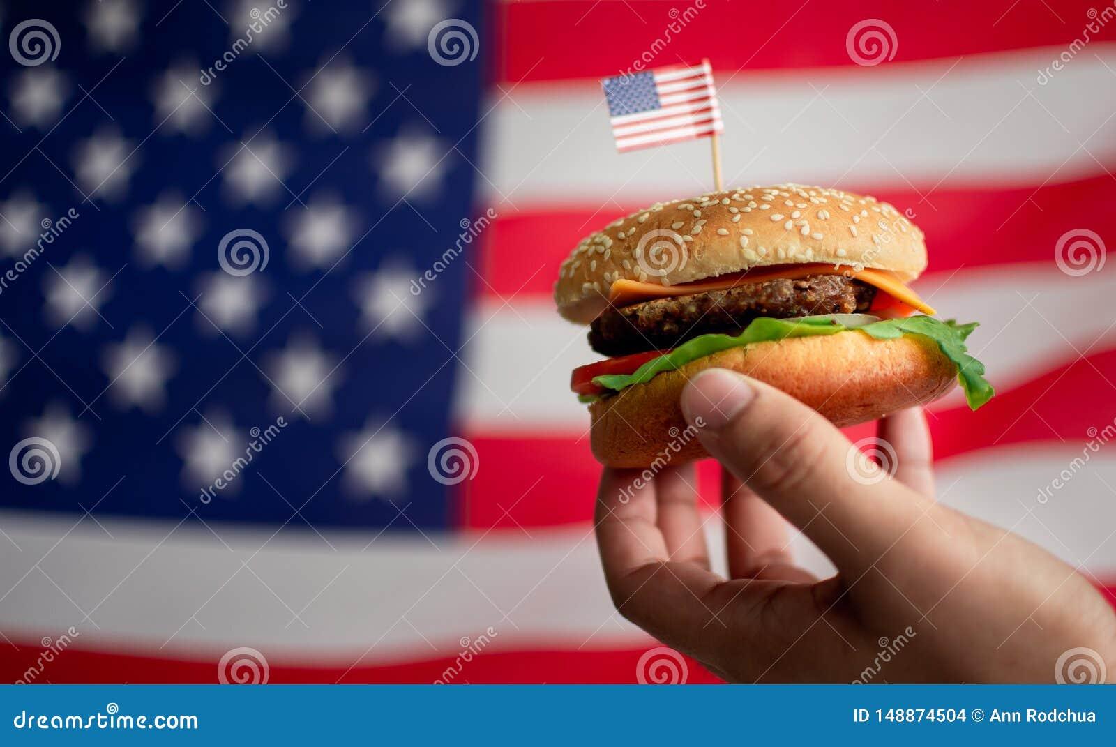 M??czyzna r?ka trzyma hamburger z t?em flaga ameryka?ska