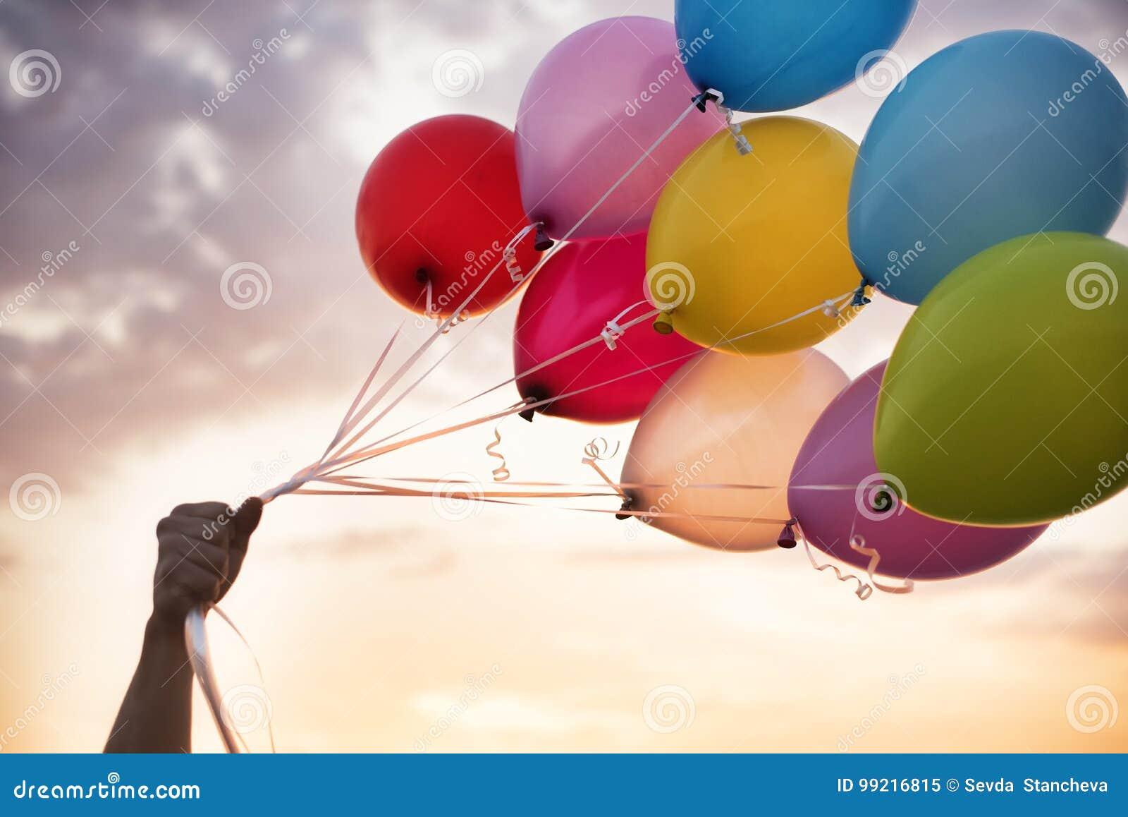 Mężczyzna ręka Trzyma Kolorowych balony I Pięknego zmierzch Przyjęcie urodzinowe balony
