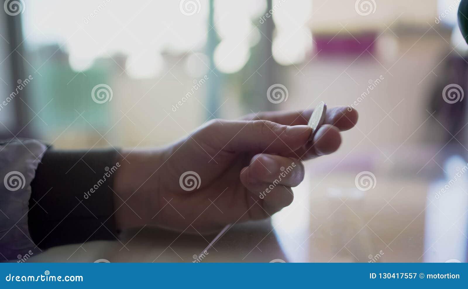 Mężczyzna ręki mienia euro moneta w palcach, próbuje robić prawej decyzji, wątpi