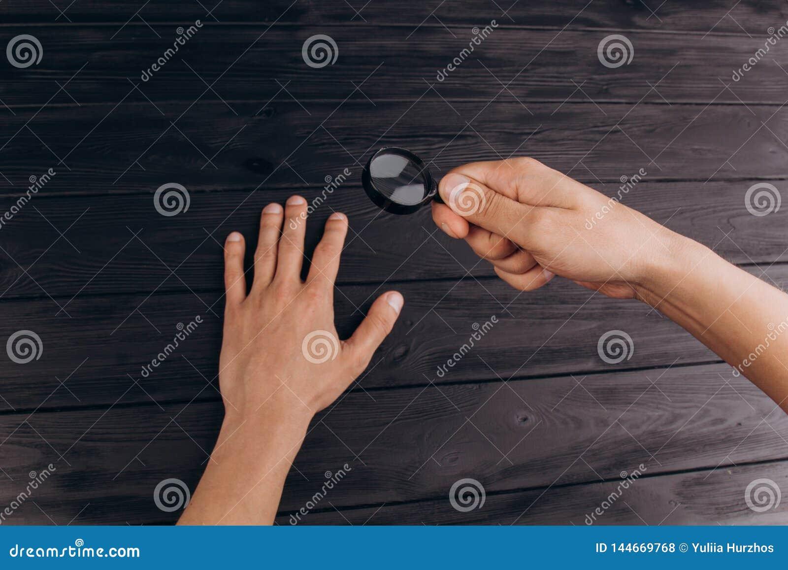 Mężczyzna ręki na nieociosanym czarnym biurku trzyma powiększać - szkło odcisk palca egzamin palmowy zbliżenie
