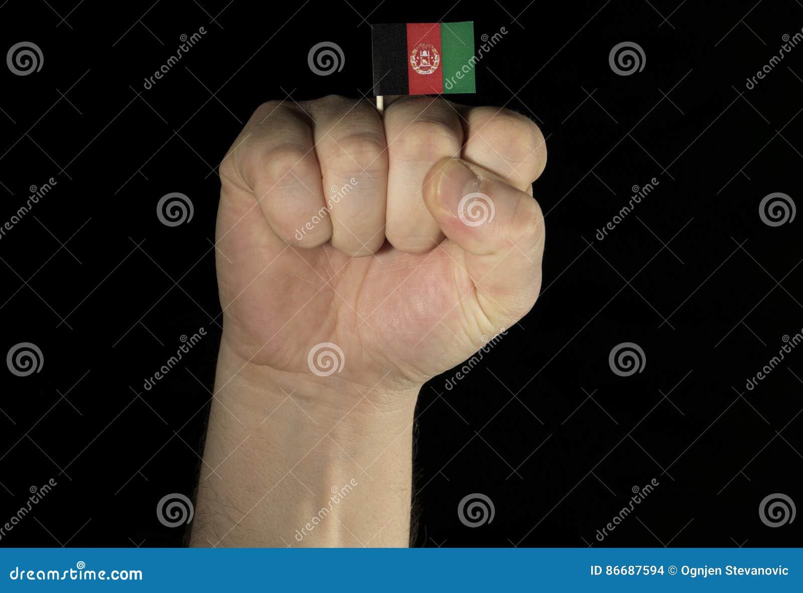 Mężczyzna ręki pięść z afgańczyk flaga odizolowywającą na czerni