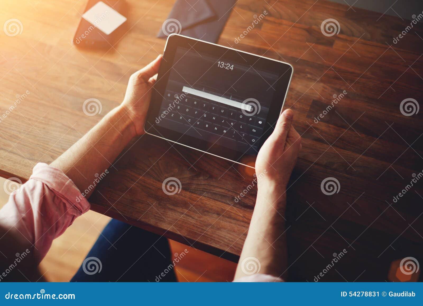Mężczyzna ręki używać cyfrową iPad pastylkę przy biurem