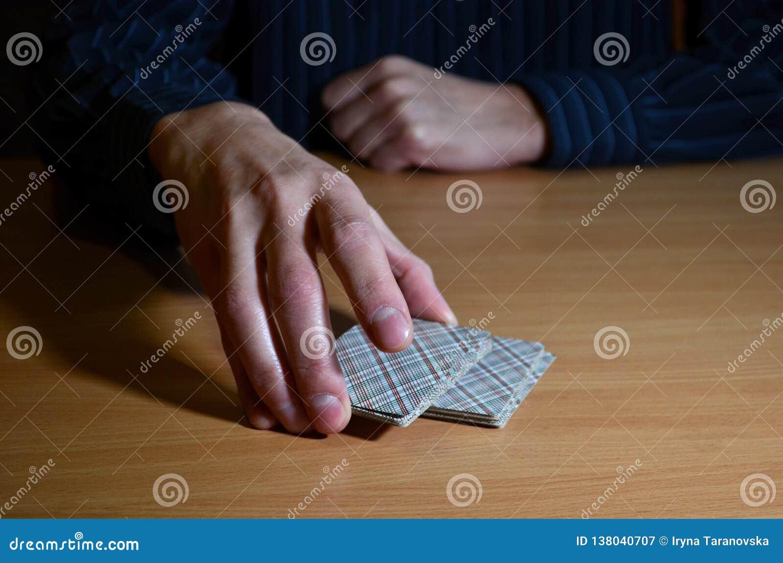 Mężczyzna ręki w ciemności stawiają część karty do gry, biznesu strategiczny turniejowy pojęcie