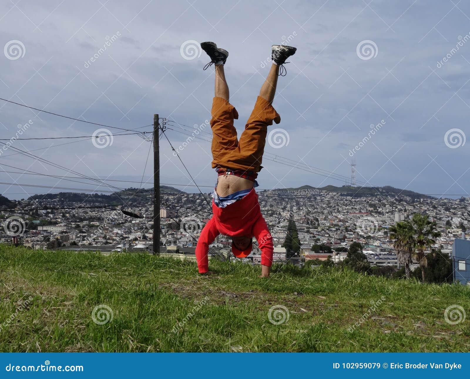 Mężczyzna robi Handstand na wierzchołku na wzgórzu przed budynkami