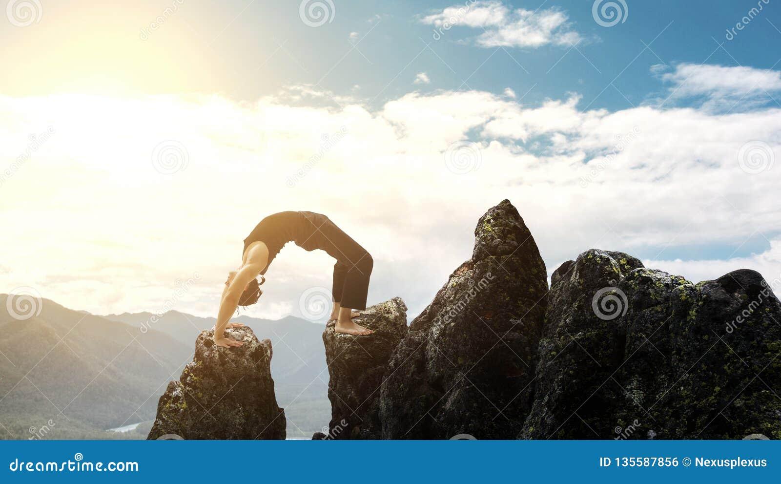 Mężczyzna robi powikłanemu joga ćwiczenia headstand Zadziwiający joga krajobraz w pięknych górach Niebezpieczny wyczynu kaskaders