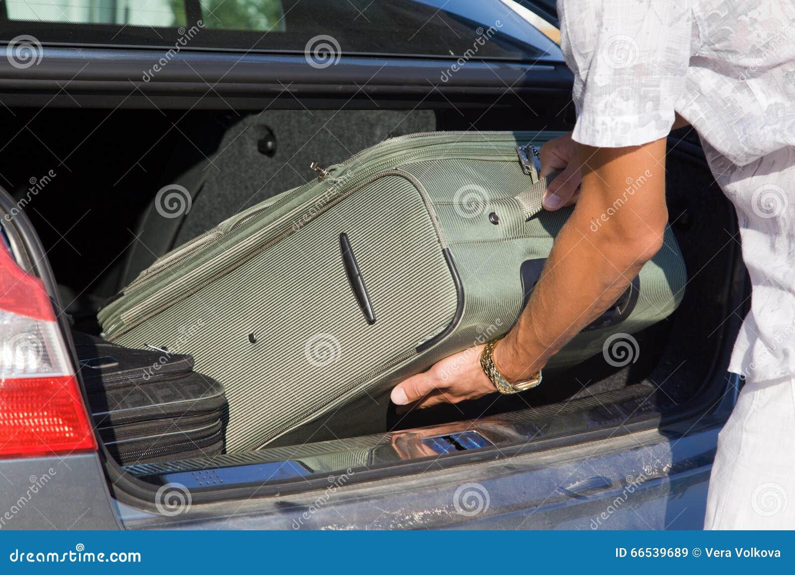 Mężczyzna rozładowywa but samochód