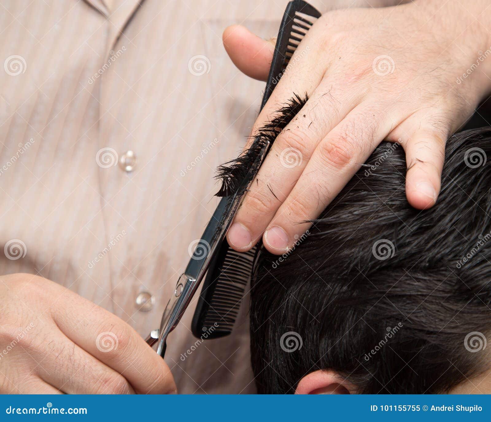 Mężczyzna ` s ostrzyżenia nożyce przy salonem