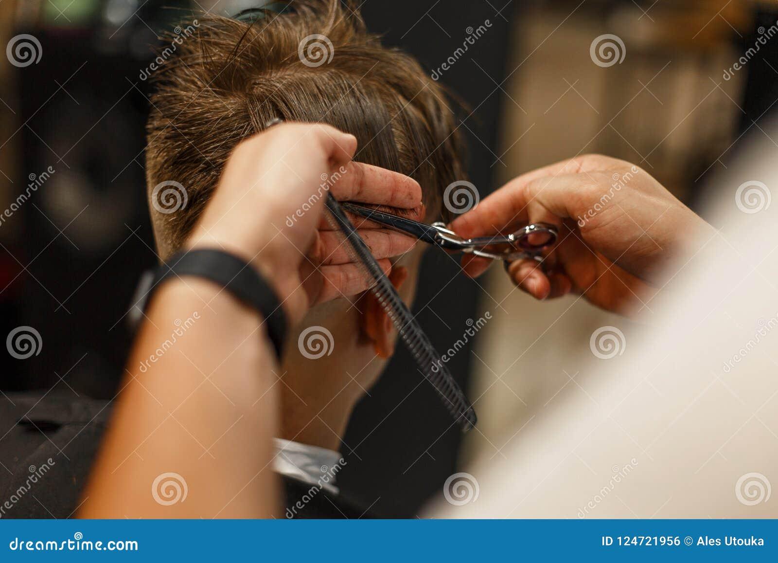 Mężczyzna ` s ostrzyżenie Fachowy fryzjer robi fryzurze