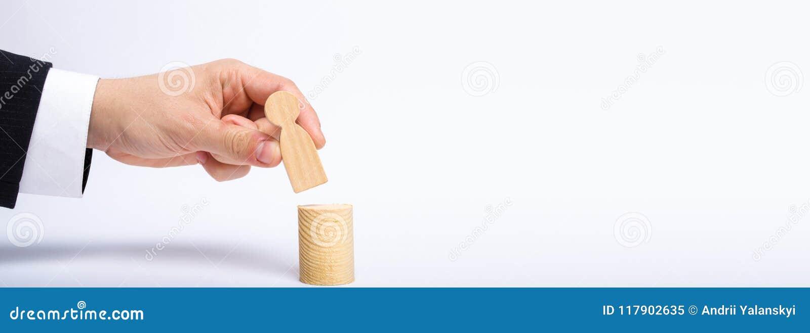 Mężczyzna ` s ręka stawia osoby ` s postać na górze jego nowego poczta A biznesmena mianuje osoby kierownicza pozycja