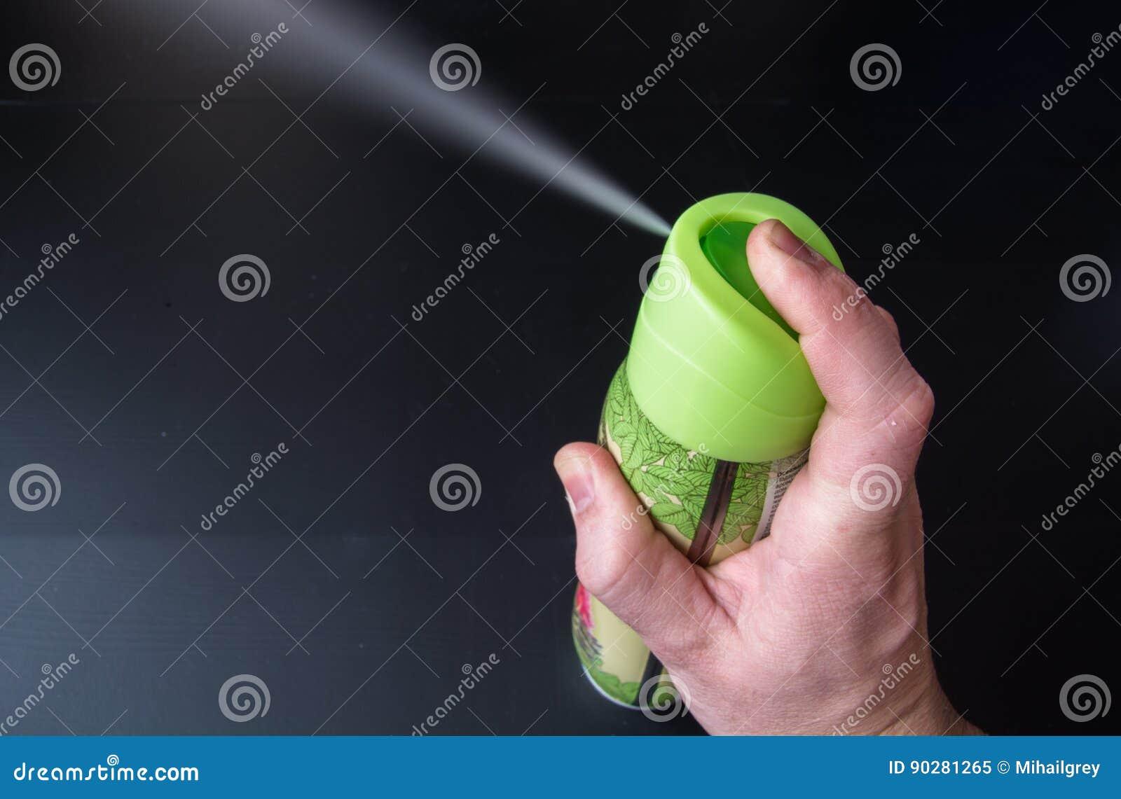 Mężczyzna ` s ręka trzyma lotniczego freshener rozpylać i butelkę