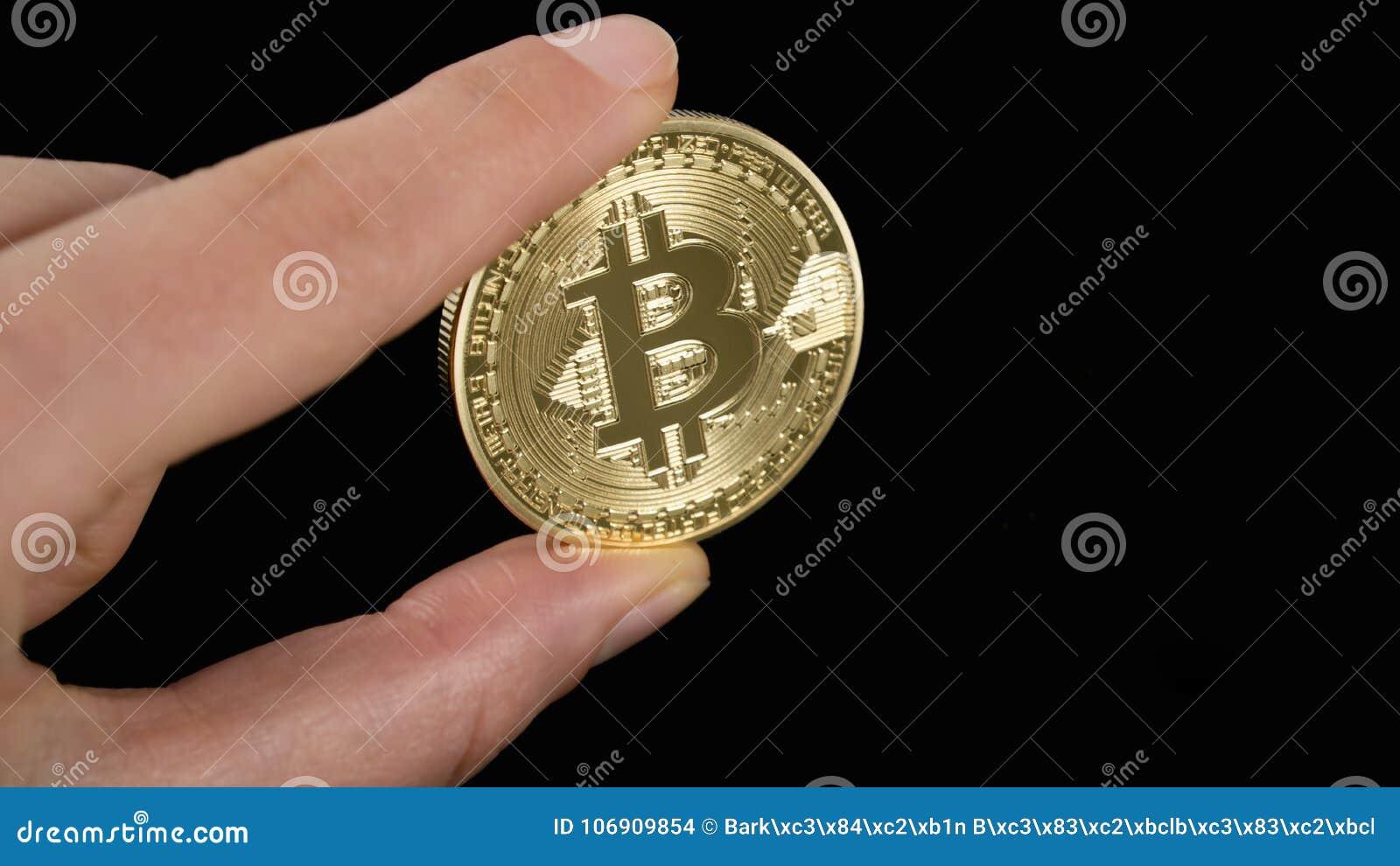 Mężczyzna ` s ręka trzyma złotego Bitcoin na czarnym tle