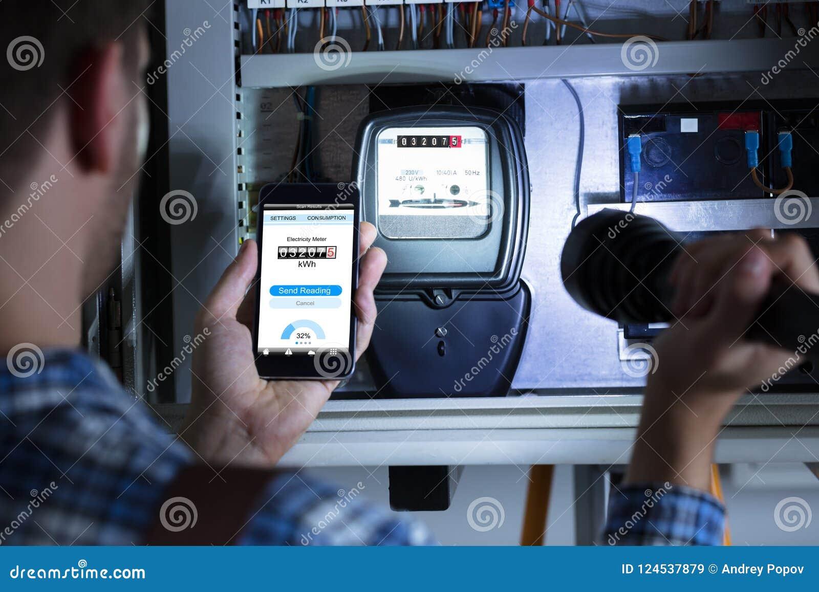 Mężczyzna ` s ręki mienia telefon komórkowy Pokazuje Elektrycznego Metrowego czytanie