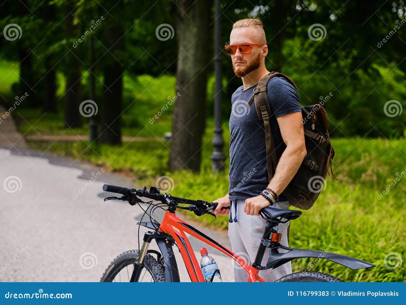Mężczyzna siedzi na czerwony halny rowerowy plenerowym