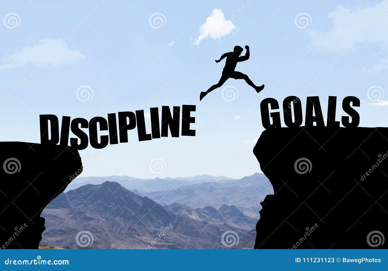 Mężczyzna skacze nad bezdennością z tekstem DISCIPLINE/GOALS
