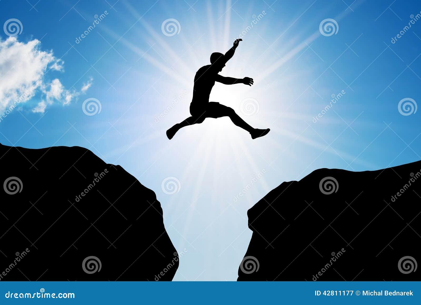 Mężczyzna skacze nad urwiskiem Ryzyko, wyzwanie, sukces